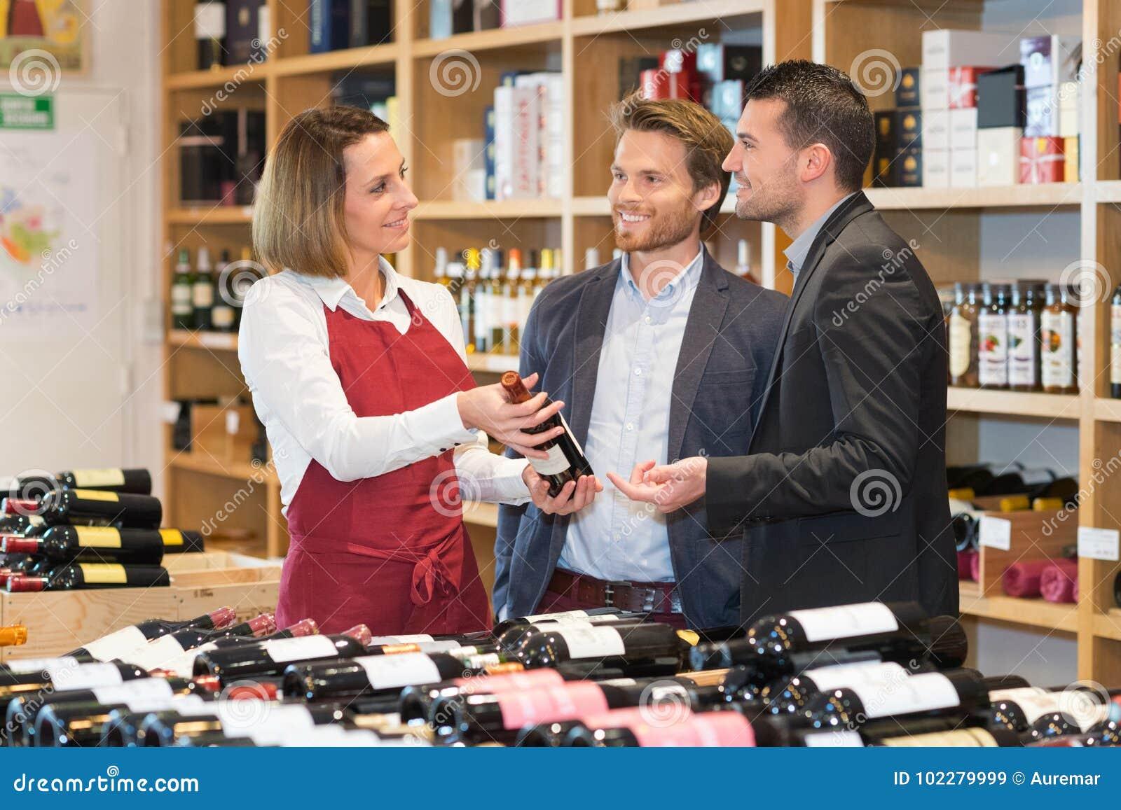 Marchandiseur et clients féminins de vin