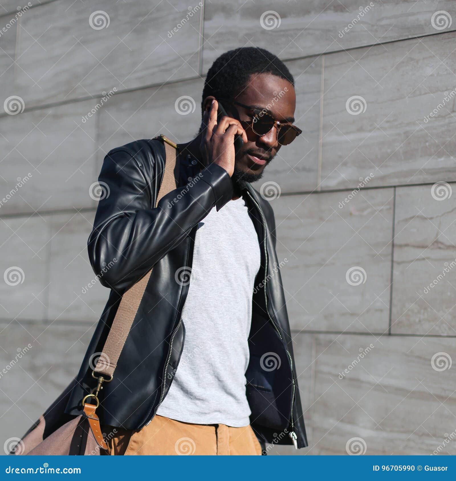 f2addf1d68a Façonnez à portrait le jeune homme africain sûr marchant et parlant sur le  smartphone dans une ville de soirée