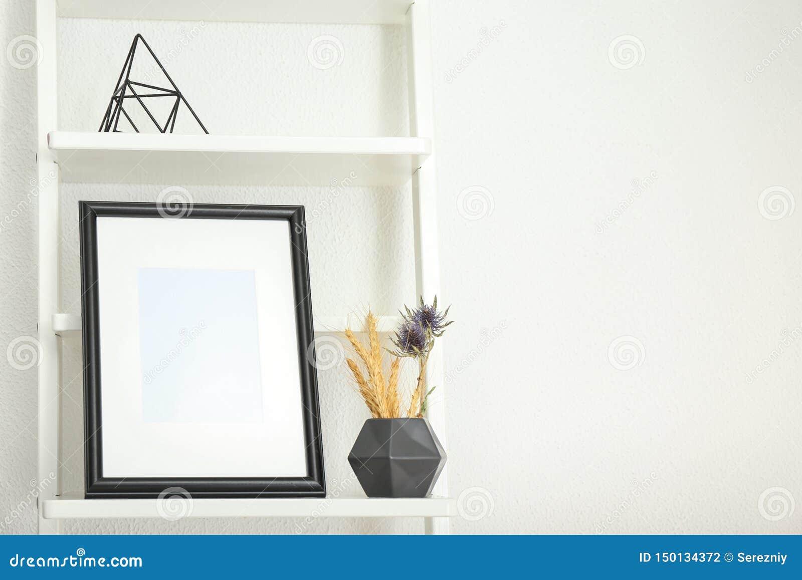 Marco de la foto con el florero en estante contra fondo ligero