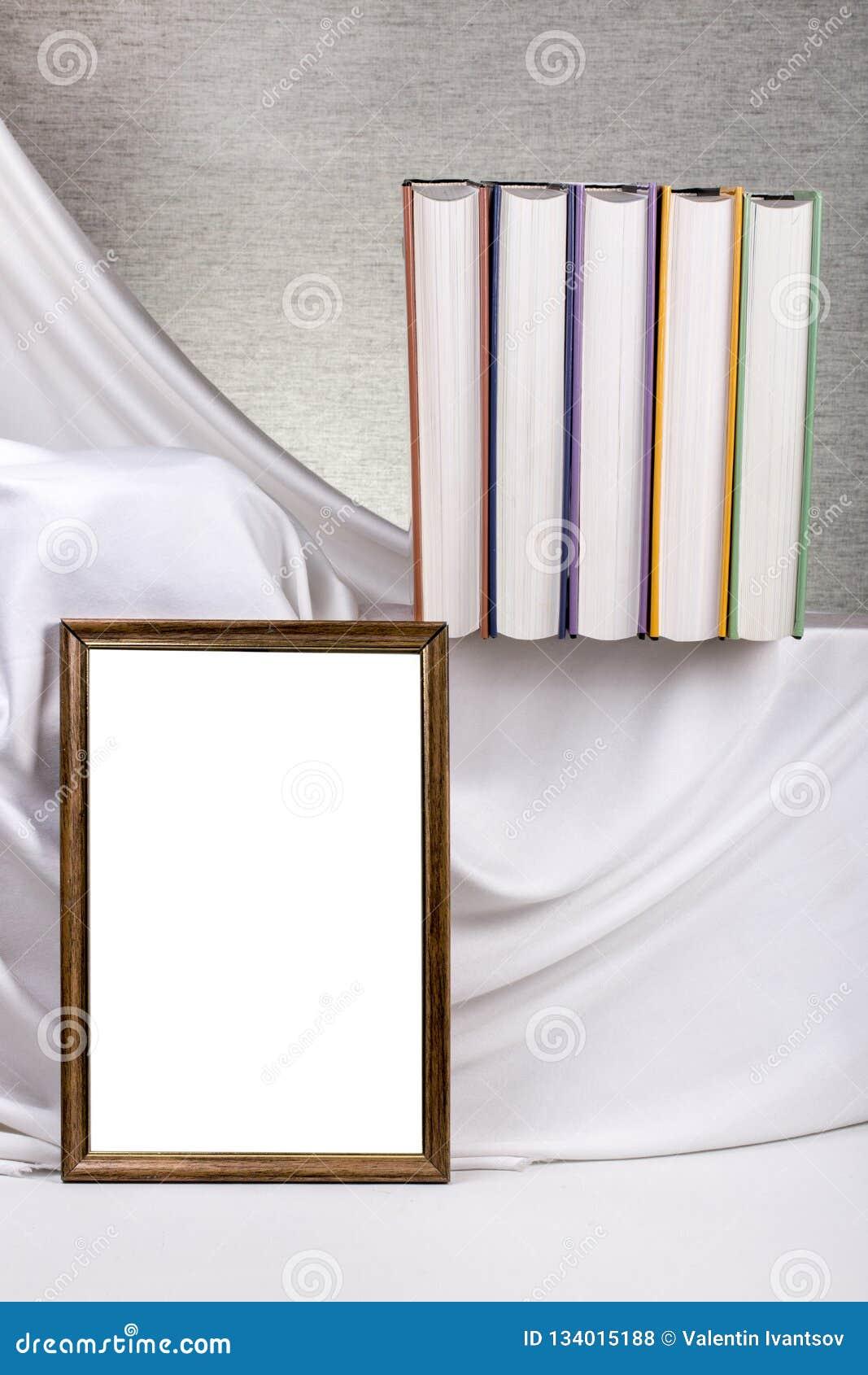 Marco de la foto para su maqueta en la tabla con los libros