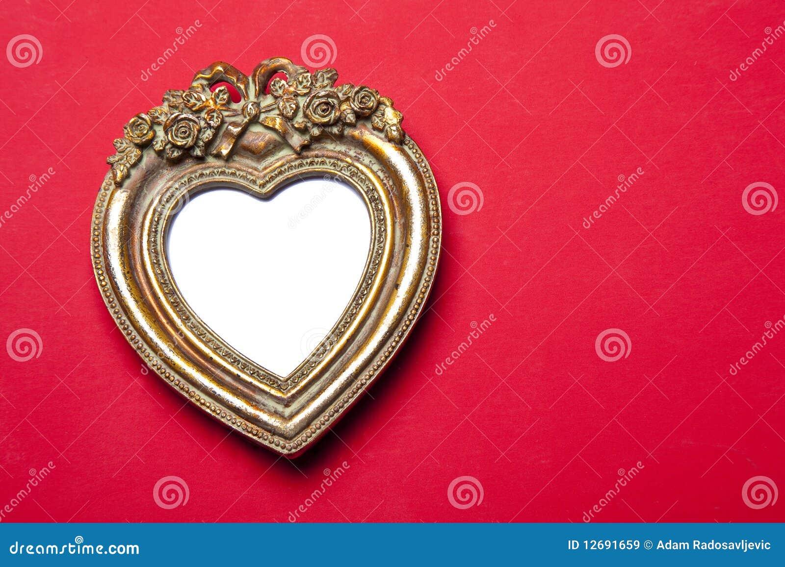 Marco del corazón del oro en rojo