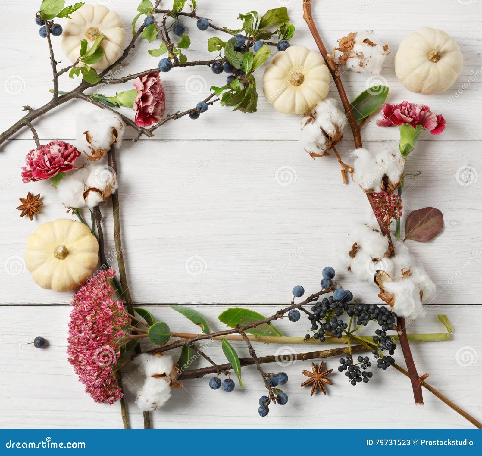 Marco del otoño de flores secadas en la madera blanca, fondo