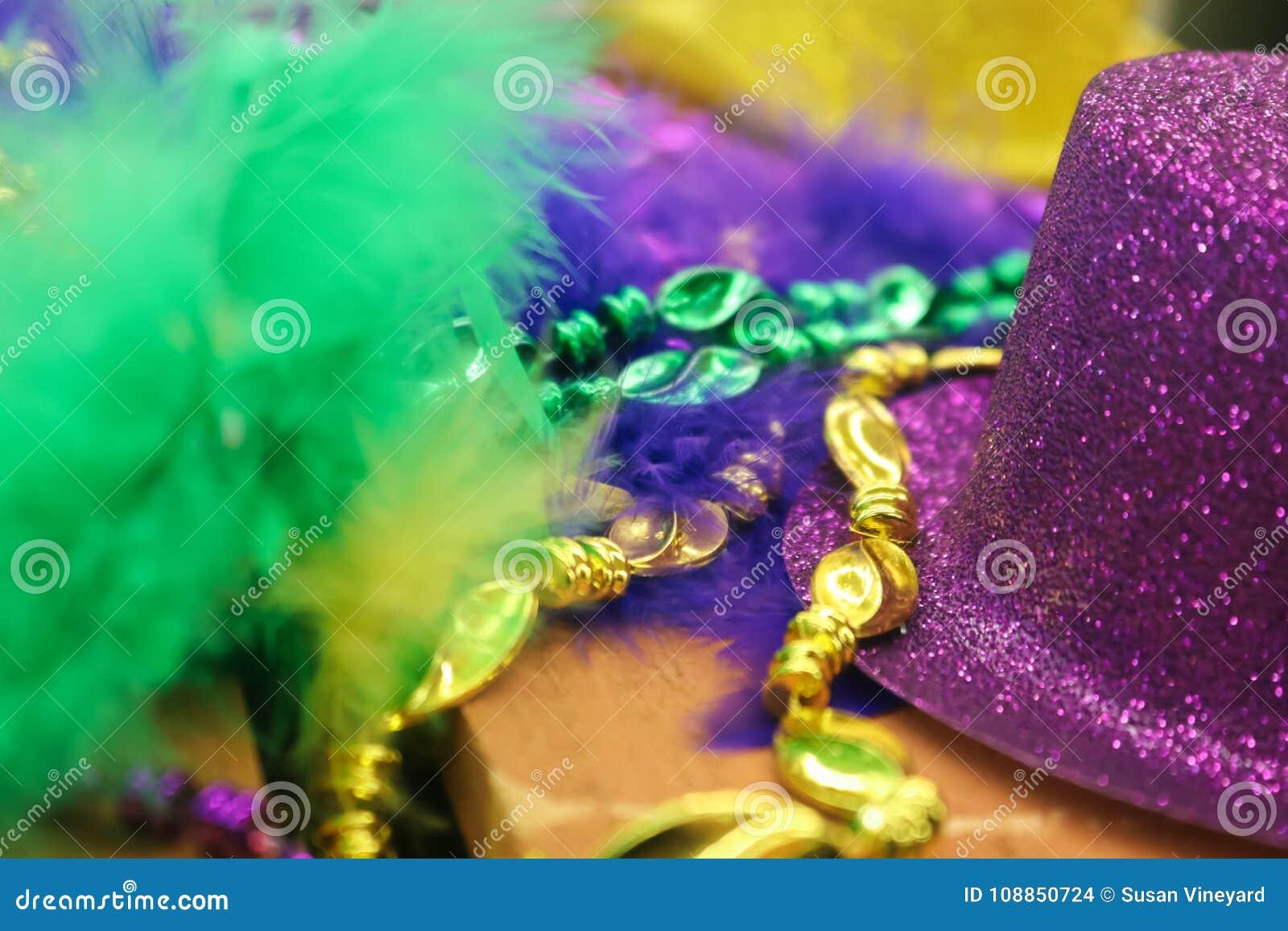 Mardi Gras bakgrund i gräsplan och skuggor av lilor och guld med fjädrar och sparkly hatt och pärlor - selektiv fokus