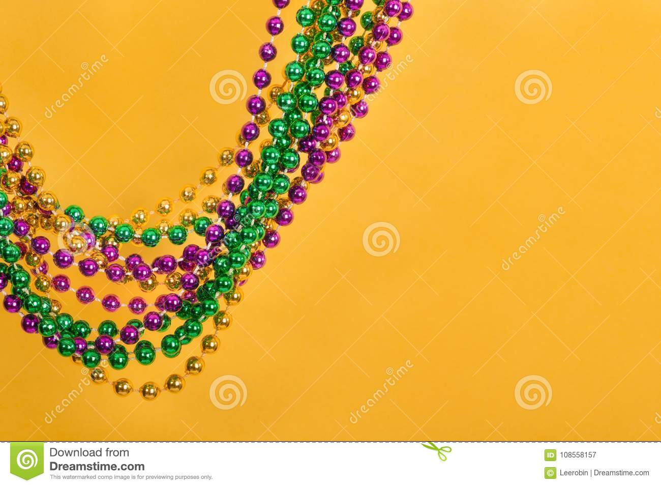 Mardi Gras beads against yellow background