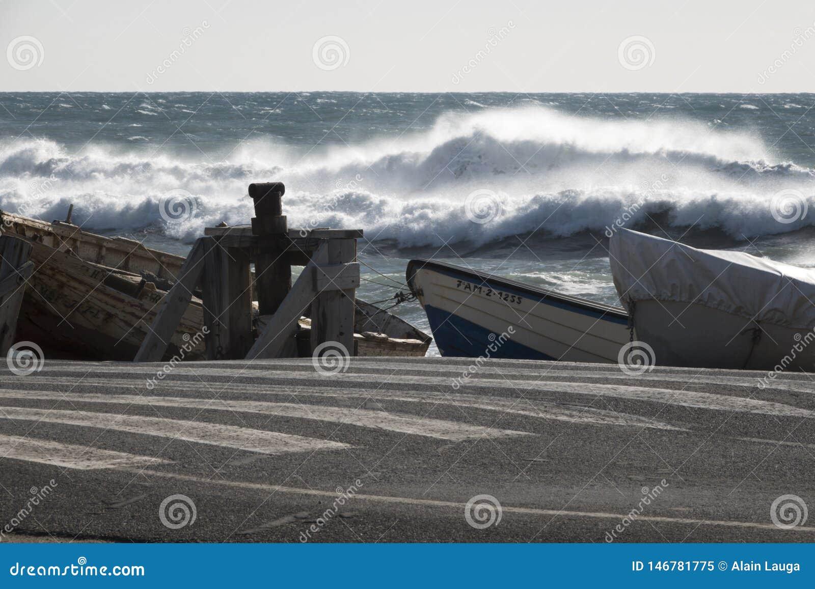 Mare tempestoso con le barche attraccate vicino alla via