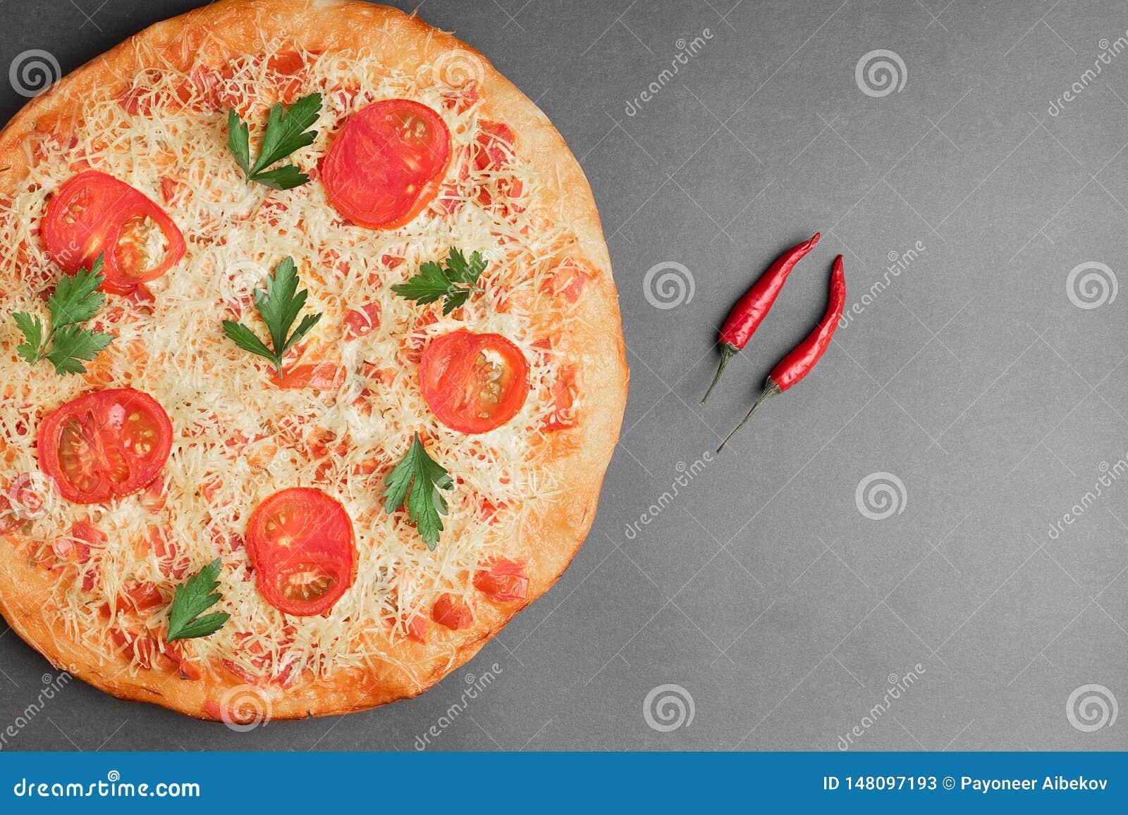 Margarita Pizza com tomate e o pimentão dois vermelho na tabela cinzenta, na vista superior e no lugar para o texto