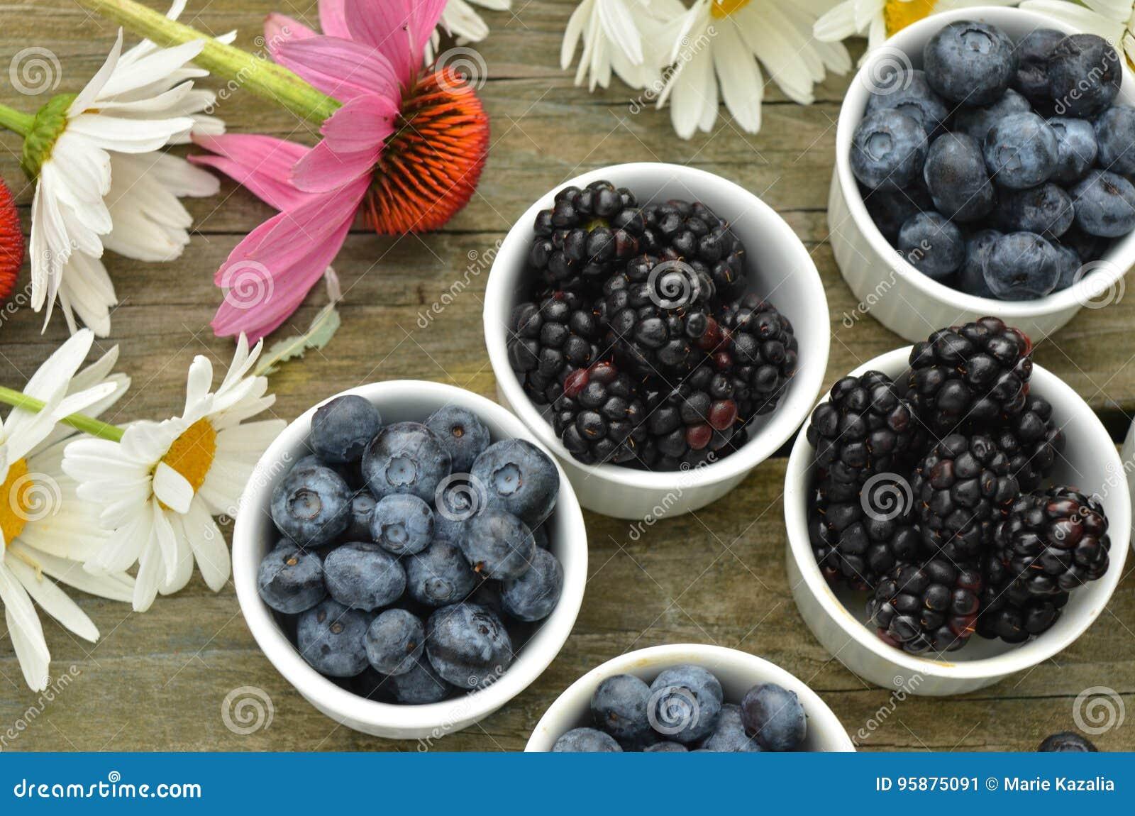 Margaritas del jardín de los arándanos y de las zarzamoras en la tabla de madera rústica