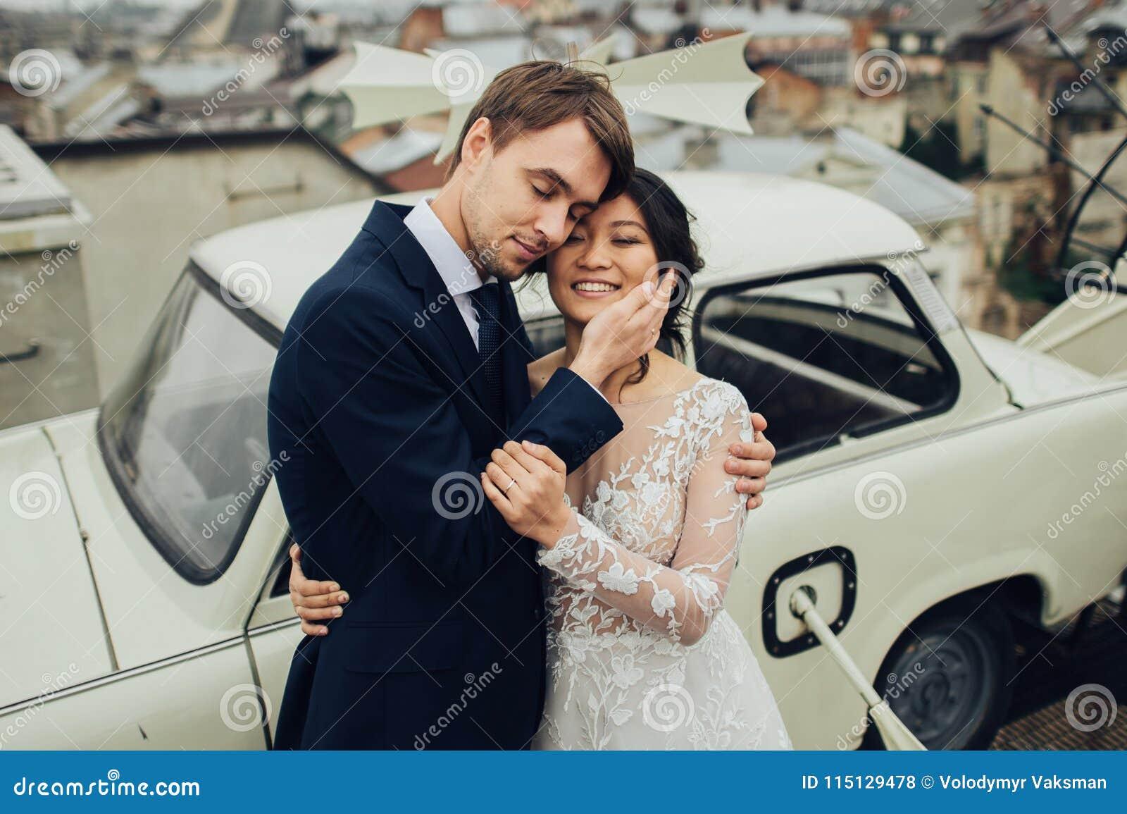 Marié avec la pose de jeune mariée extérieure dans le jour du mariage