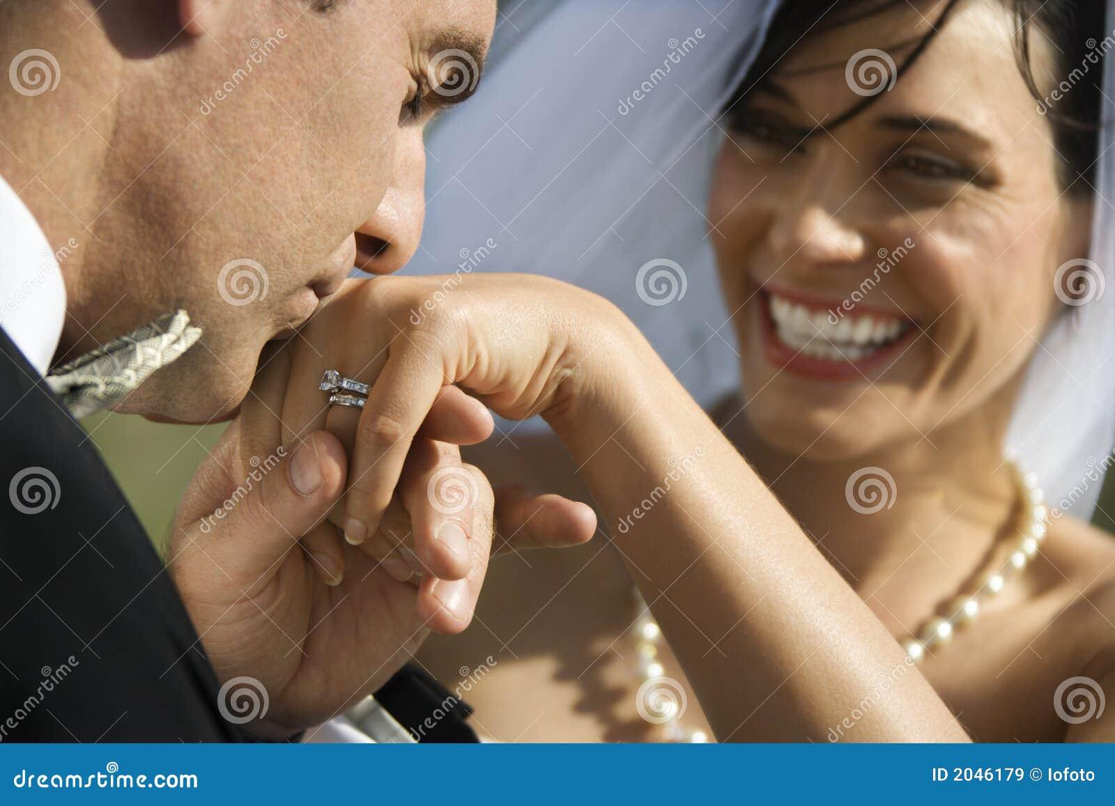 Marié embrassant la main de la mariée