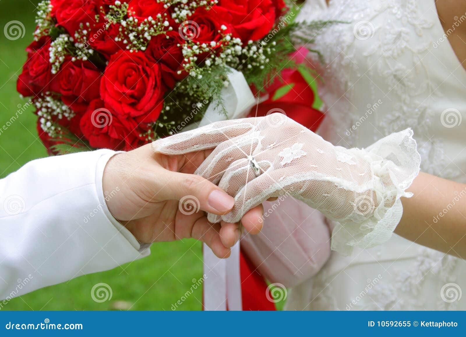 Marié retenant sa main gauche de mariée (juste mariée)