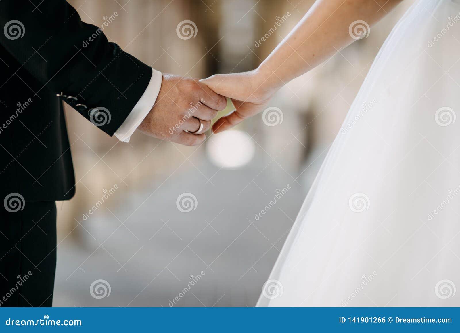 Marié tenant la main de la jeune mariée tout en marchant