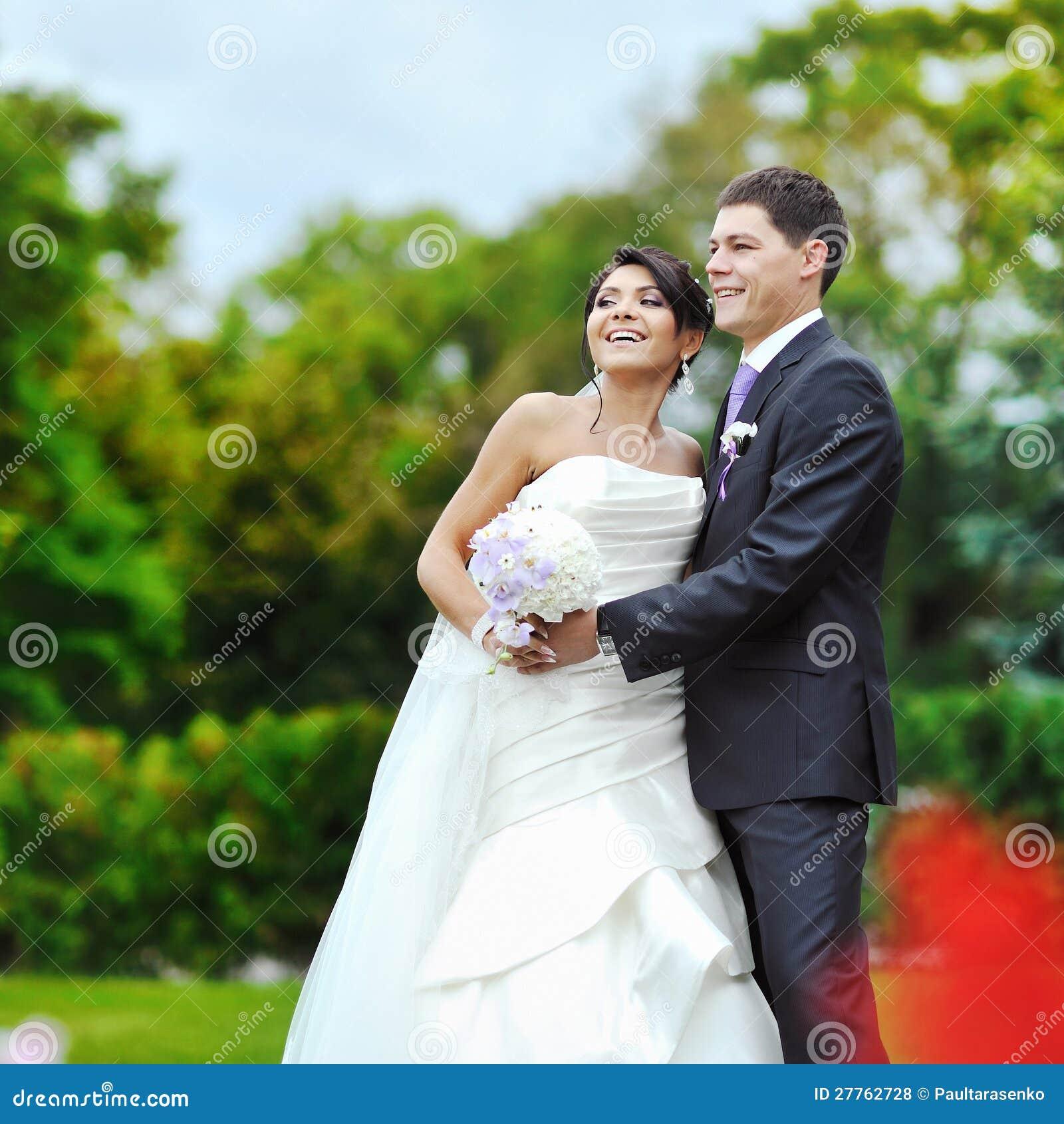 Mariée et marié heureux en stationnement. Couples de mariage