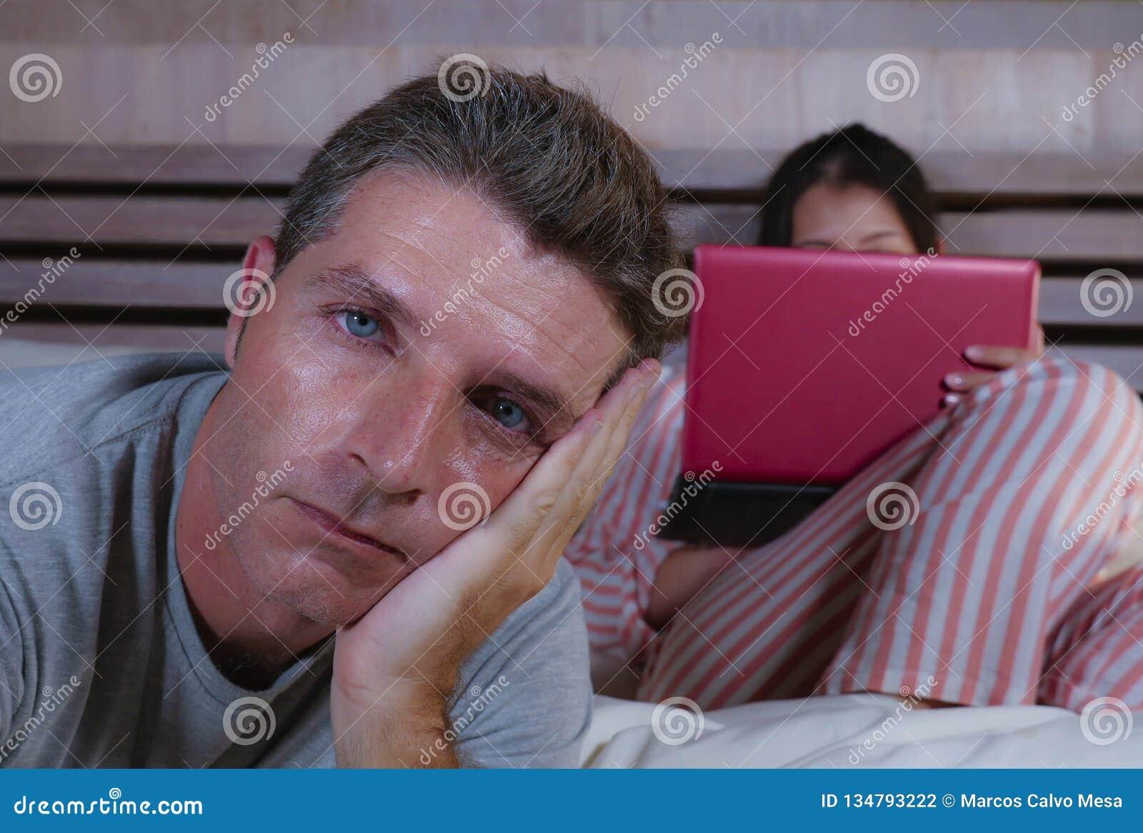 Mari fâché et frustrant déprimé dans le lit ignoré par son amie sociale d épouse de bourreau de travail ou d intoxiqué de médias