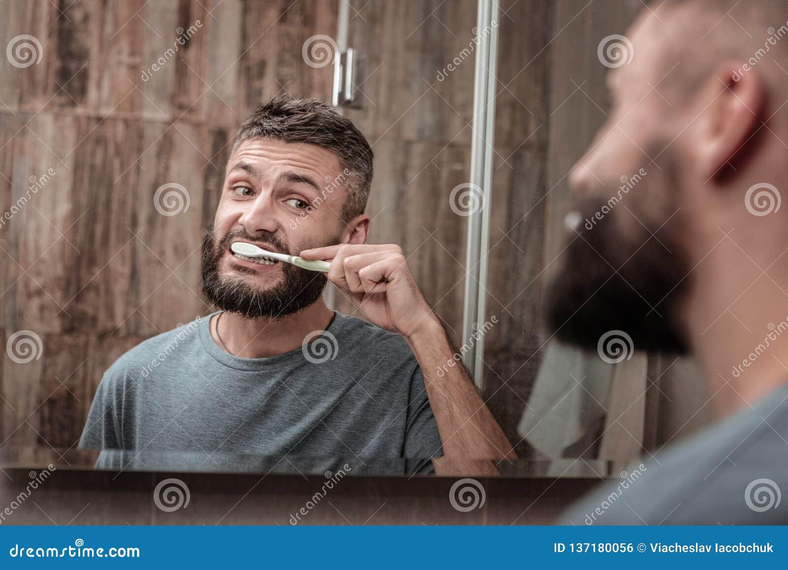Marido de olhos escuros que olha no espelho ao escovar seus dentes