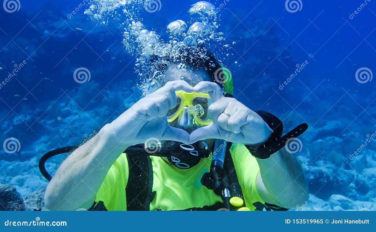Marido del buceo con escafandra que dice a su esposa que él ama su submarino