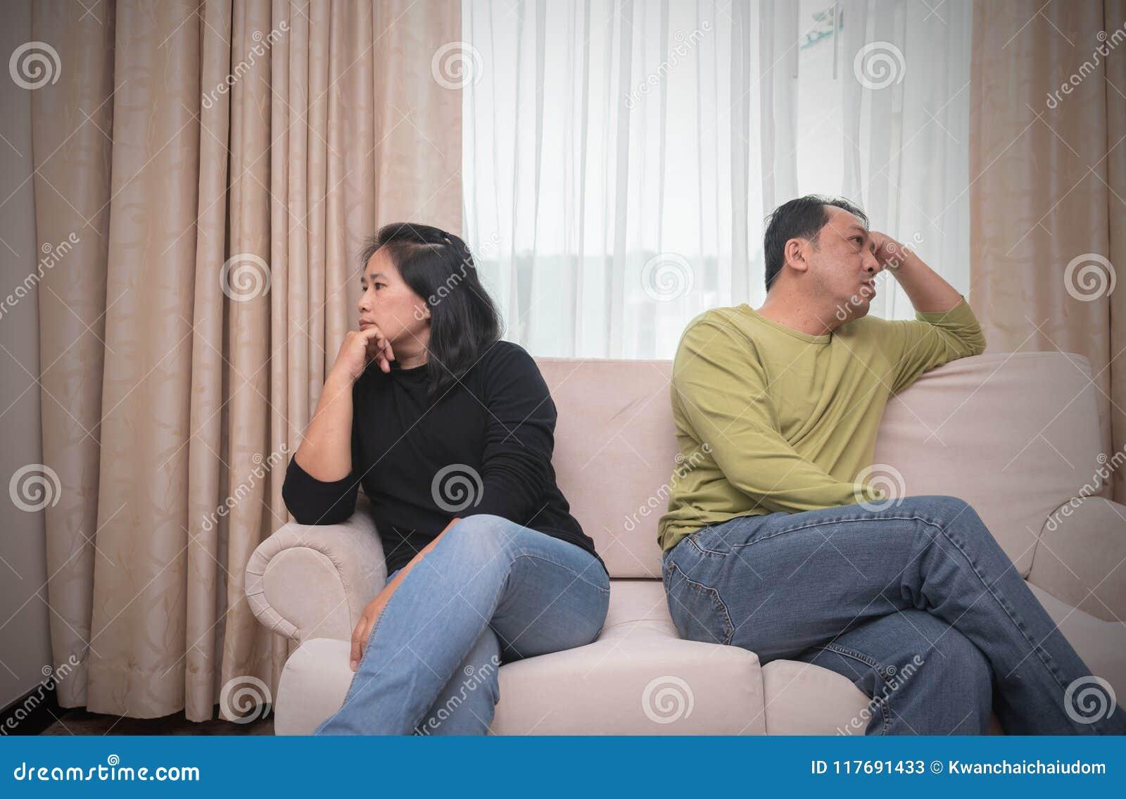 Marido e esposa que sentam-se em lados diferentes do sofá engodo da discussão