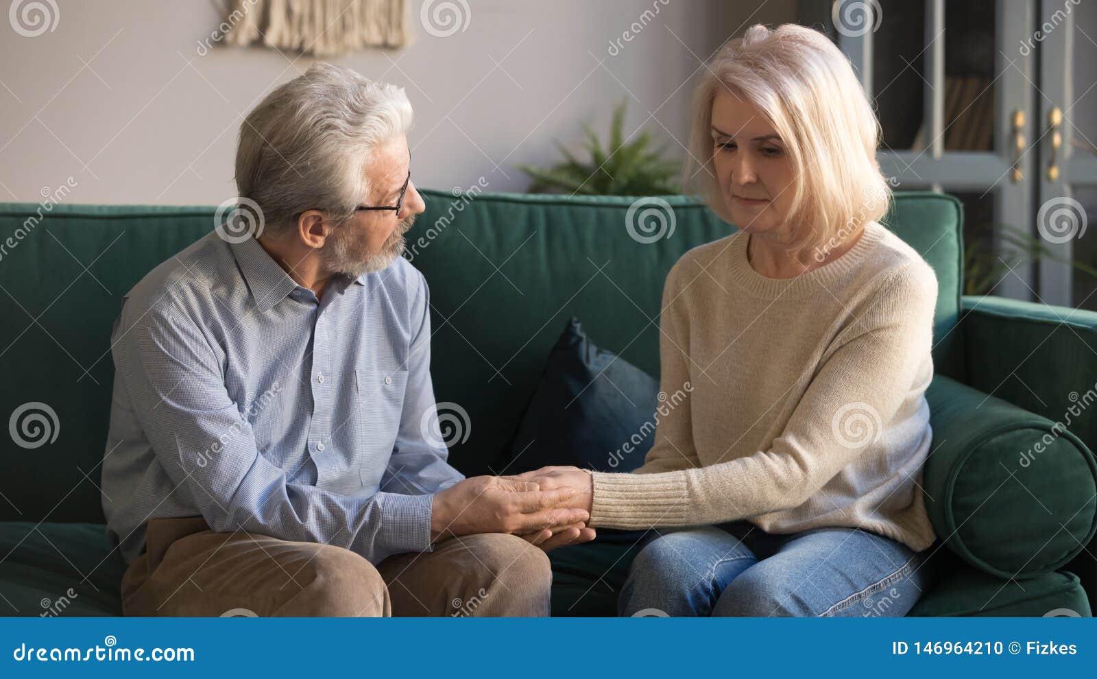Marido envelhecido médio que guarda as mãos, esposa virada de acariciamento em casa