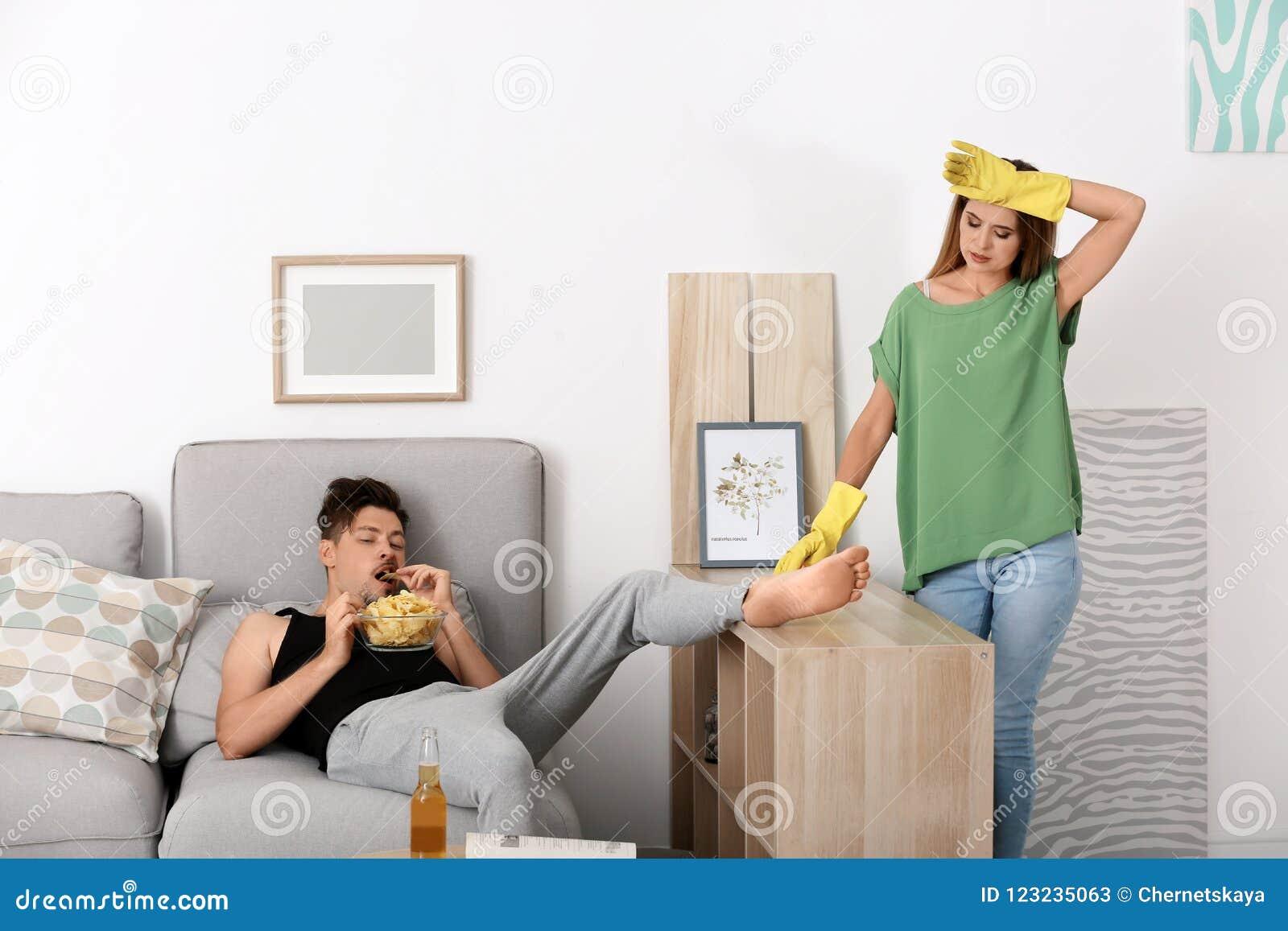 Marido perezoso que miente en el sofá y su limpieza de la esposa