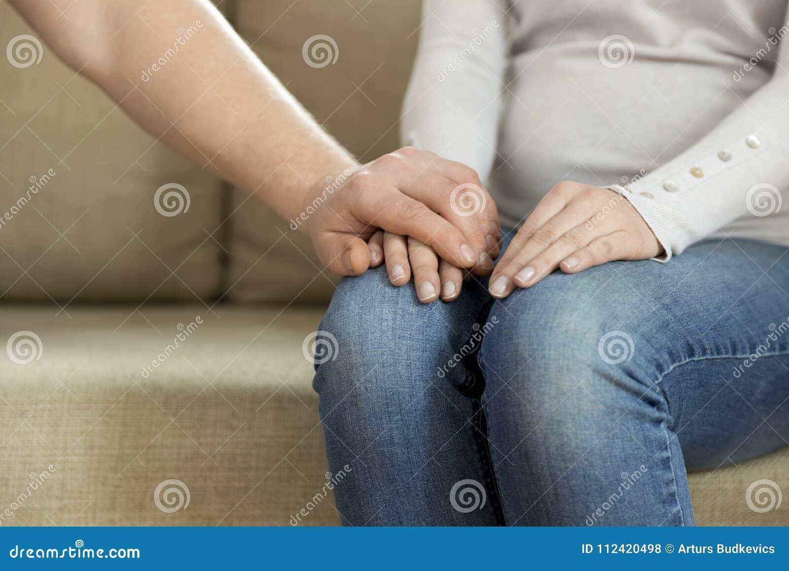 Marido que lleva a cabo la mano de su esposa, dando la ayuda emocional Ment