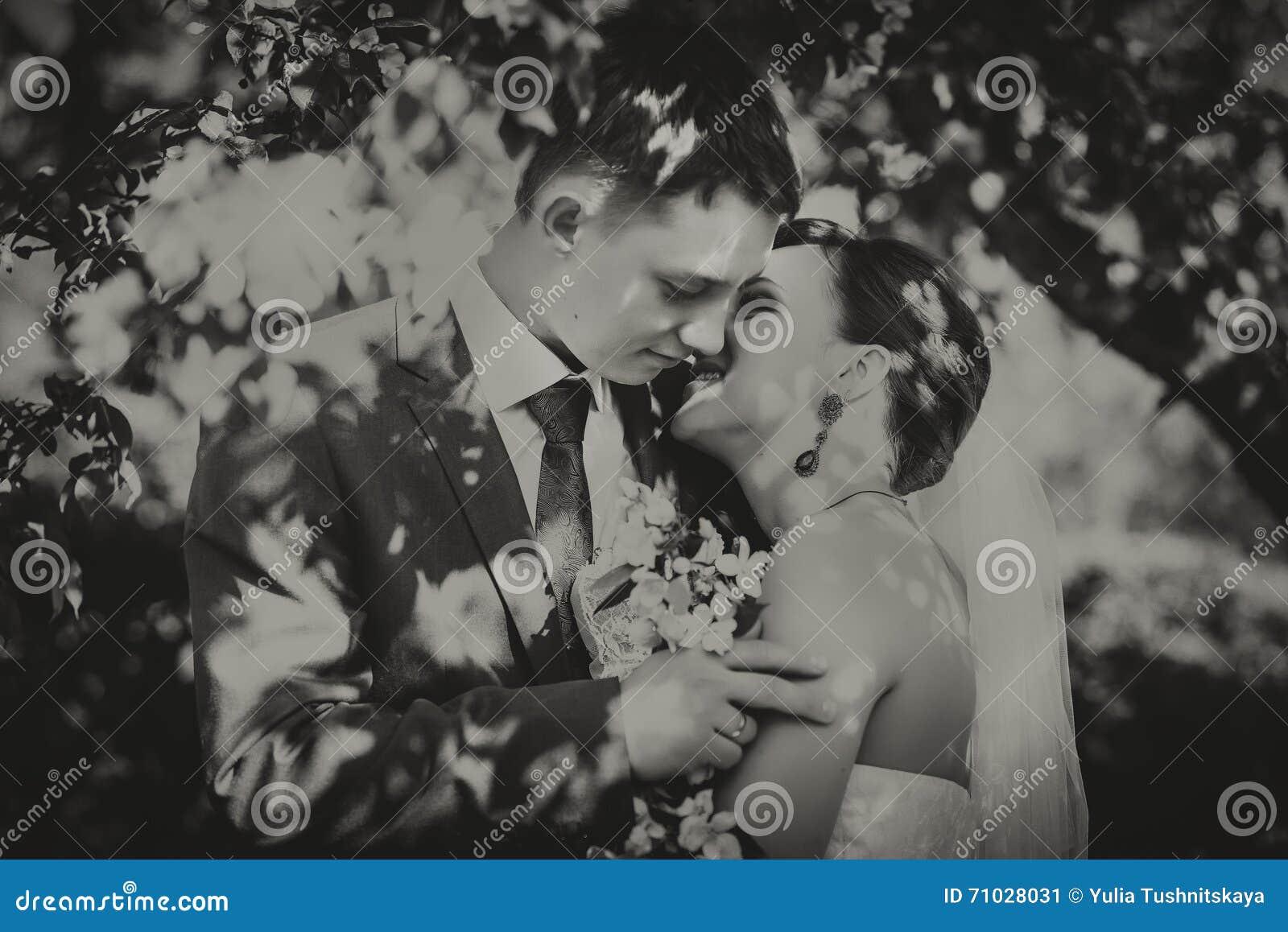 Marido y esposa jovenes felices, en flores, miran el ramo Fotografía blanca negra