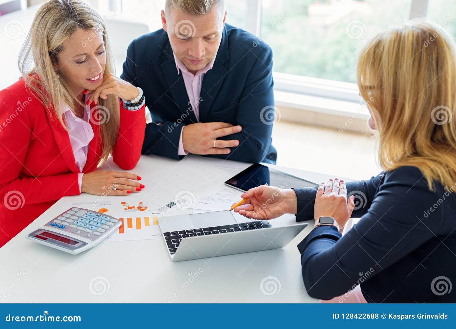 Marido y esposa que discuten planes de inversión con el consejero financiero