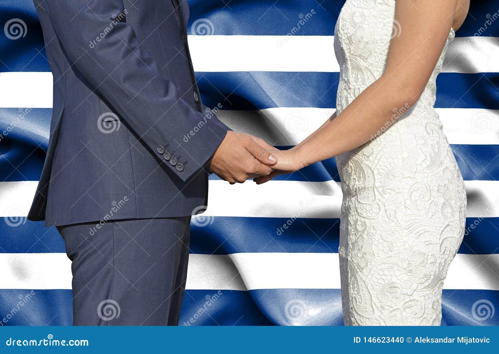 Marido y esposa que llevan a cabo las manos - fotografía conceptual del matrimonio en Grecia