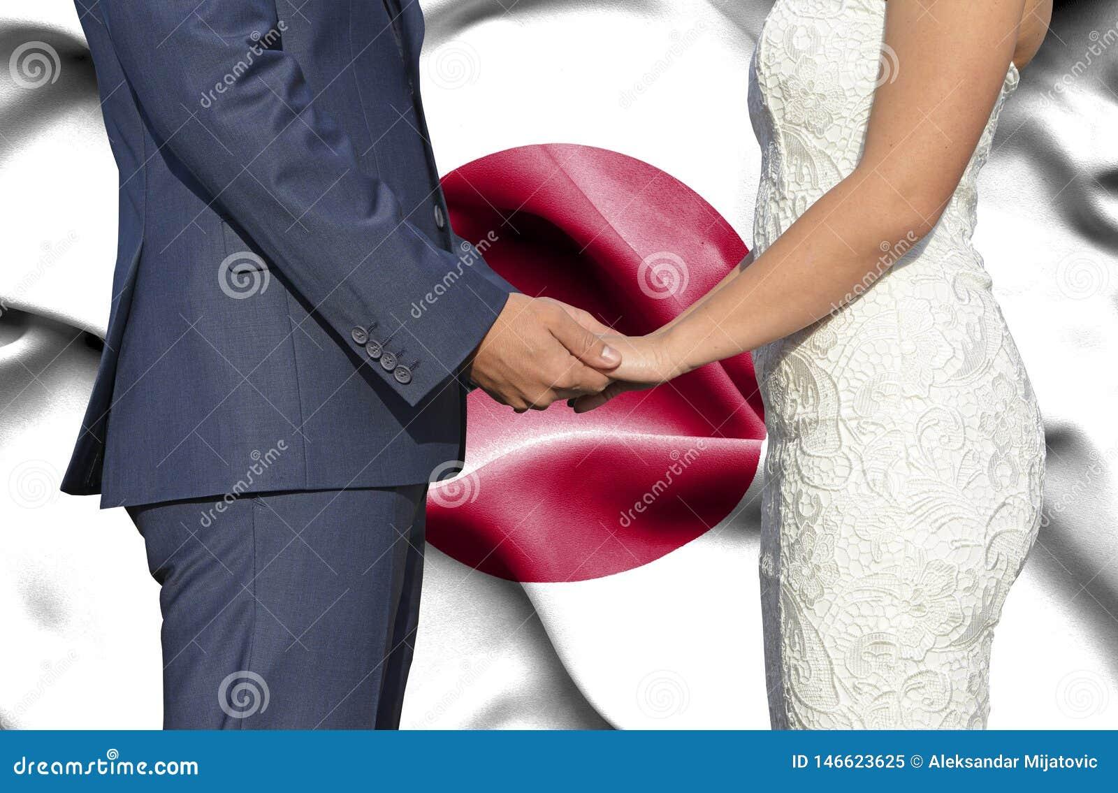 Marido y esposa que llevan a cabo las manos - fotografía conceptual del matrimonio en Japón