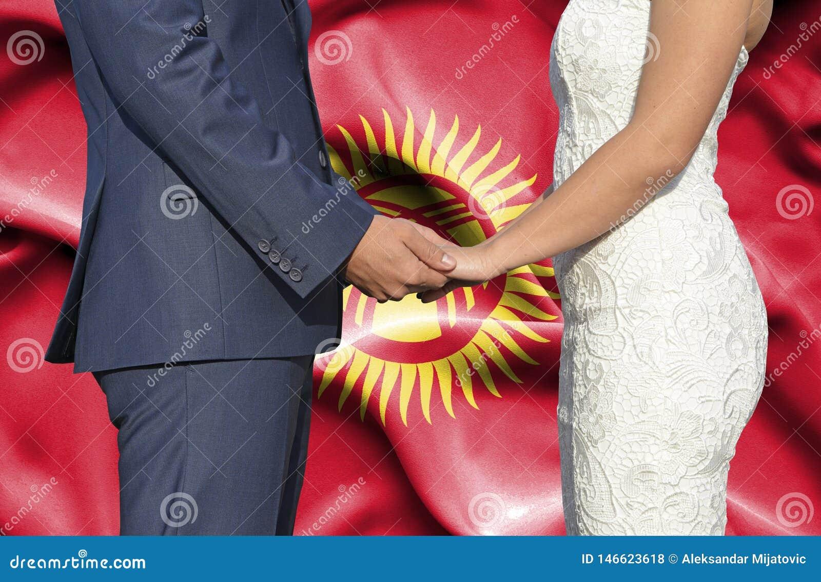 Marido y esposa que llevan a cabo las manos - fotografía conceptual del matrimonio en Krygyzstan
