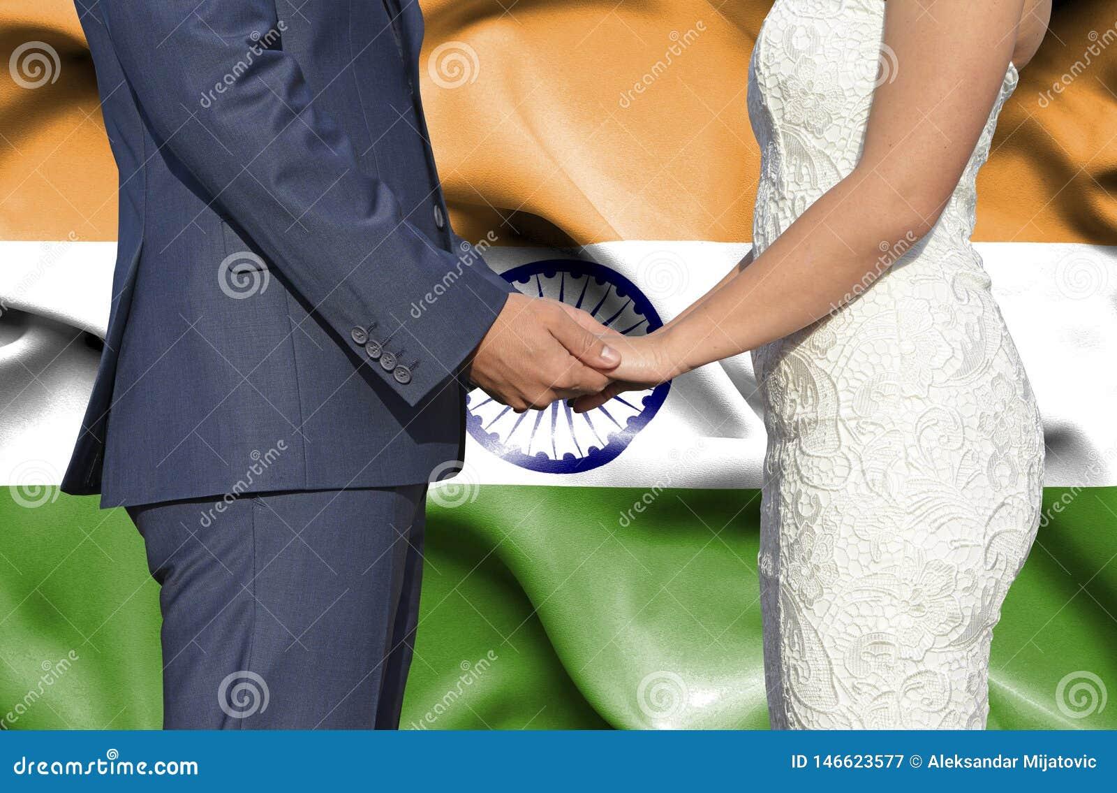 Marido y esposa que llevan a cabo las manos - fotografía conceptual del matrimonio en la India