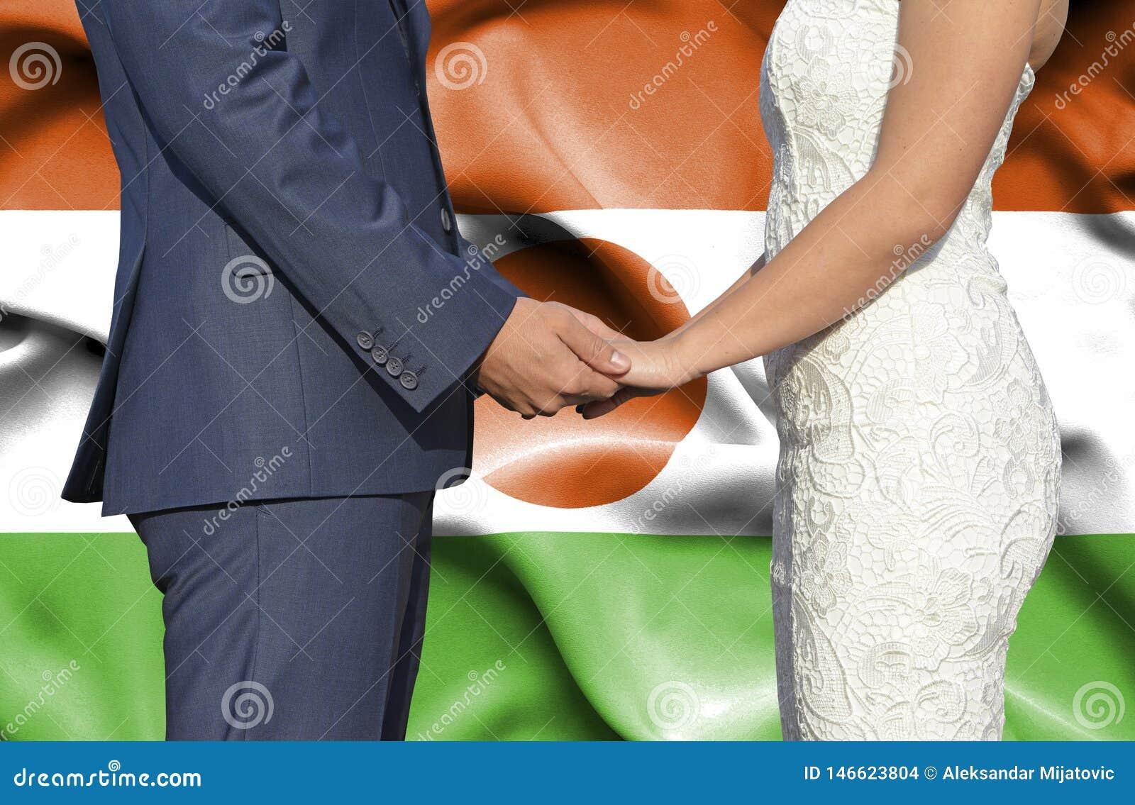 Marido y esposa que llevan a cabo las manos - fotografía conceptual del matrimonio en Niger