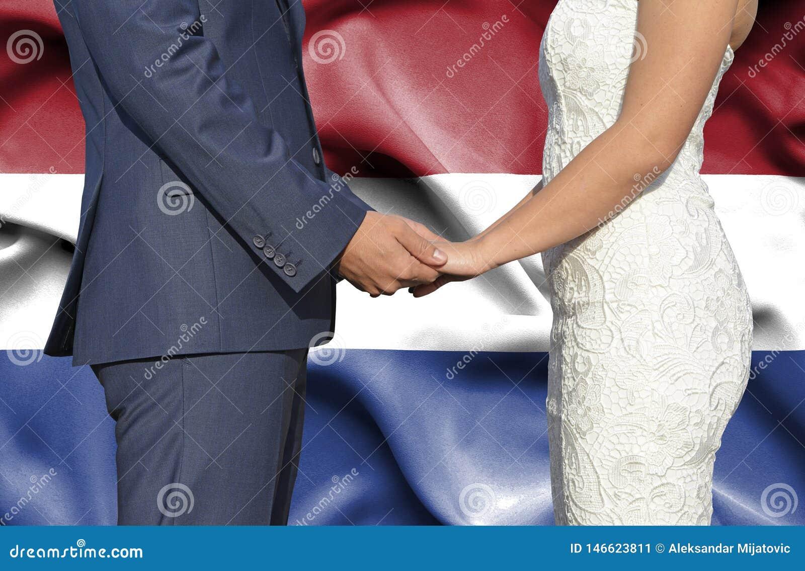 Marido y esposa que llevan a cabo las manos - fotografía conceptual del matrimonio en Países Bajos