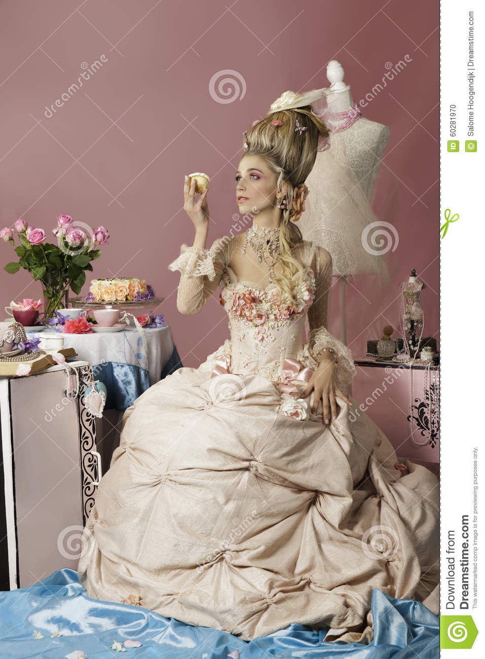 marie antoinette in pink holding a cupcake stock photo