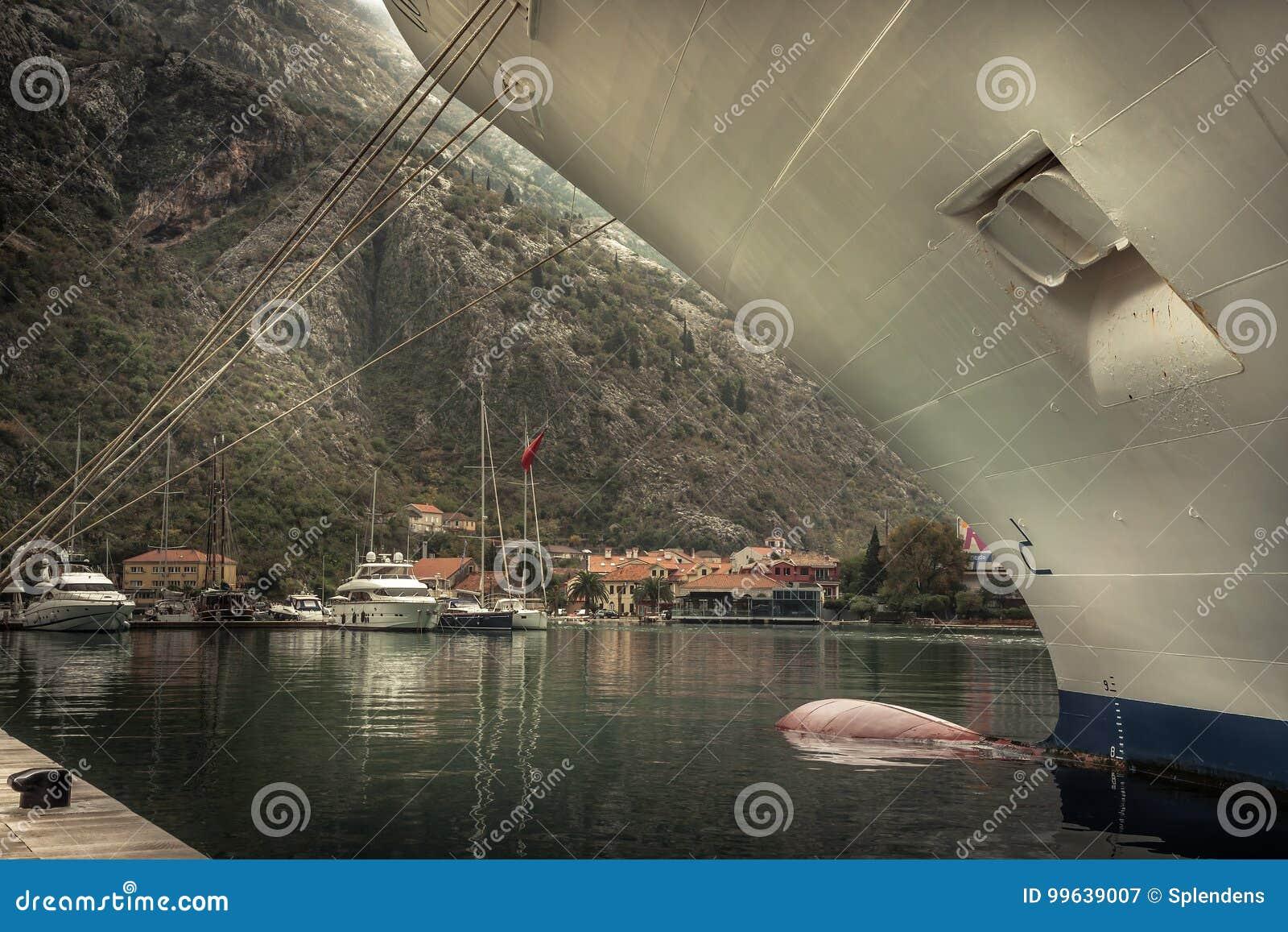 Mariene zeehaven met vastgelegd cruise zeevaartschip in middeleeuwse Kotor-baai in Montenegro in donkere regenachtige de herfstda