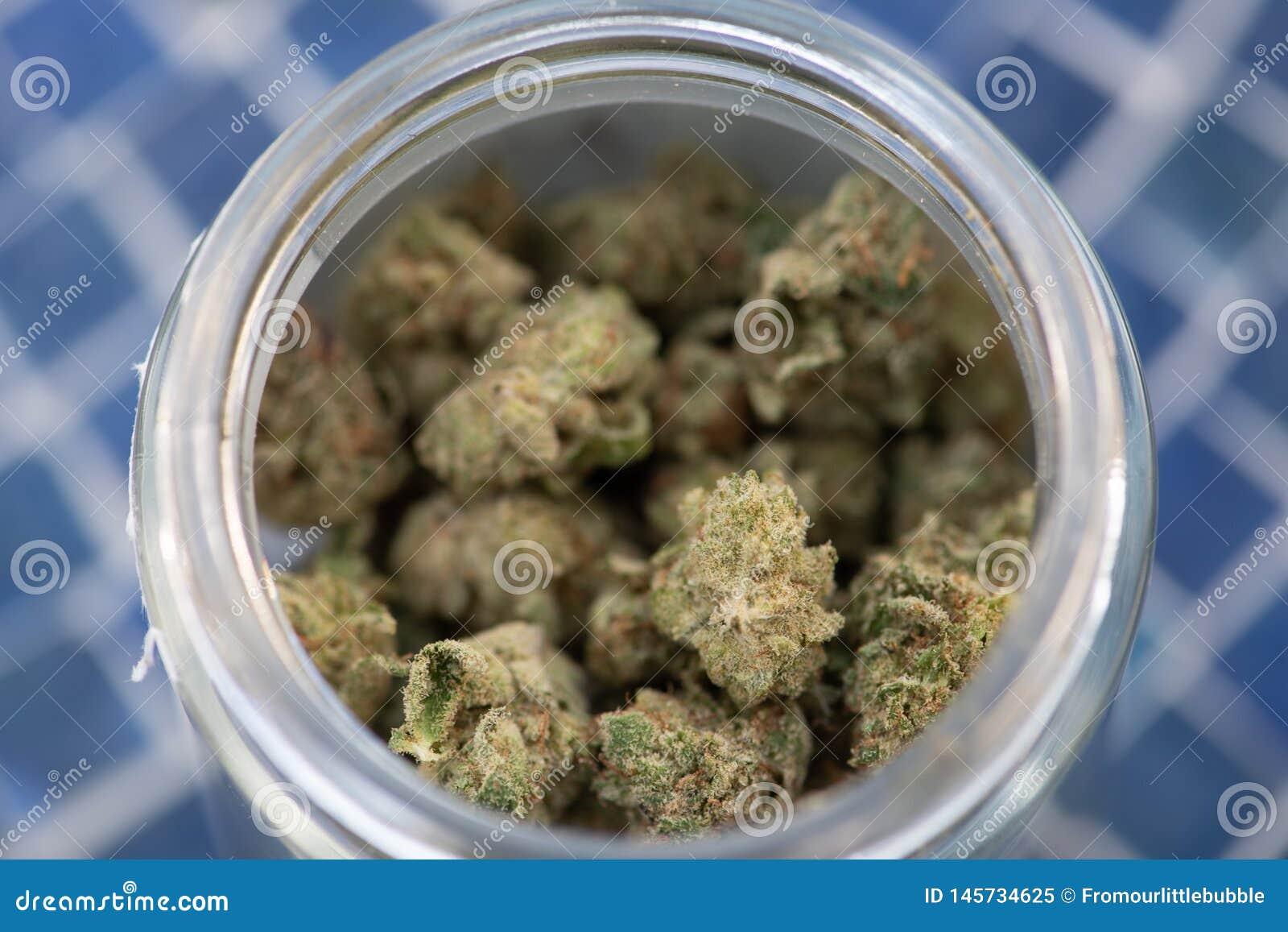 Marijuana récréationnelle dans le pot en verre sur la tuile bleue