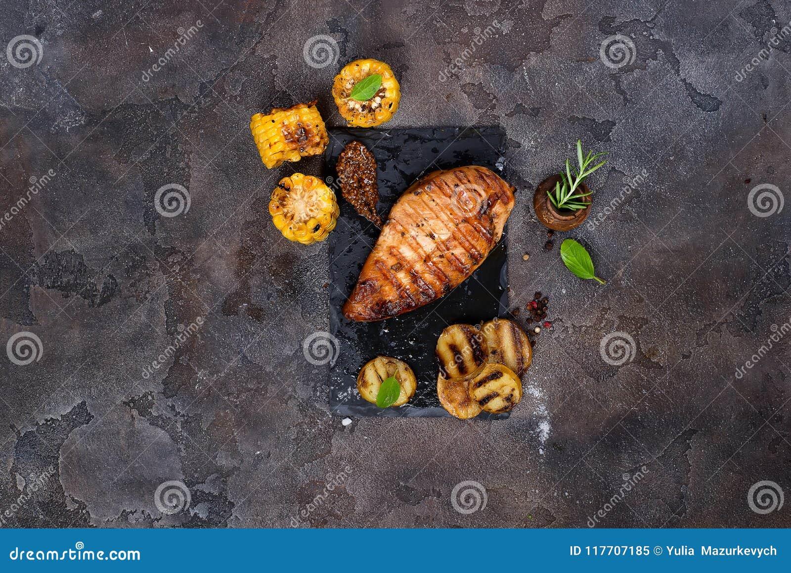 Marinated a grillé les blancs de poulet sains cuits sur un BBQ d été et servis avec les herbes, les pommes de terre et le maïs fr