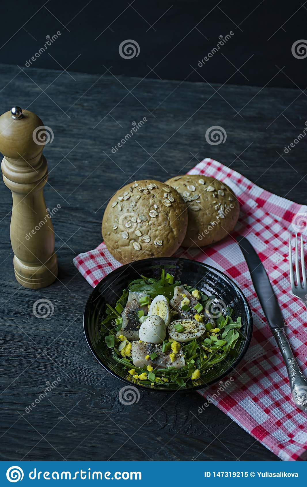 Marinated herring with arugula, onions, boiled quail eggs and lemon juice and olive oil. Delicious salad. Proper nutrition. Dark