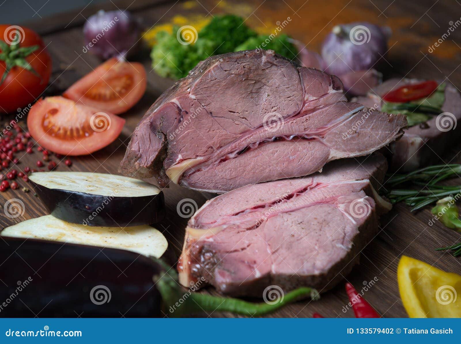 Marinating мясо и свежие овощи на деревянном столе