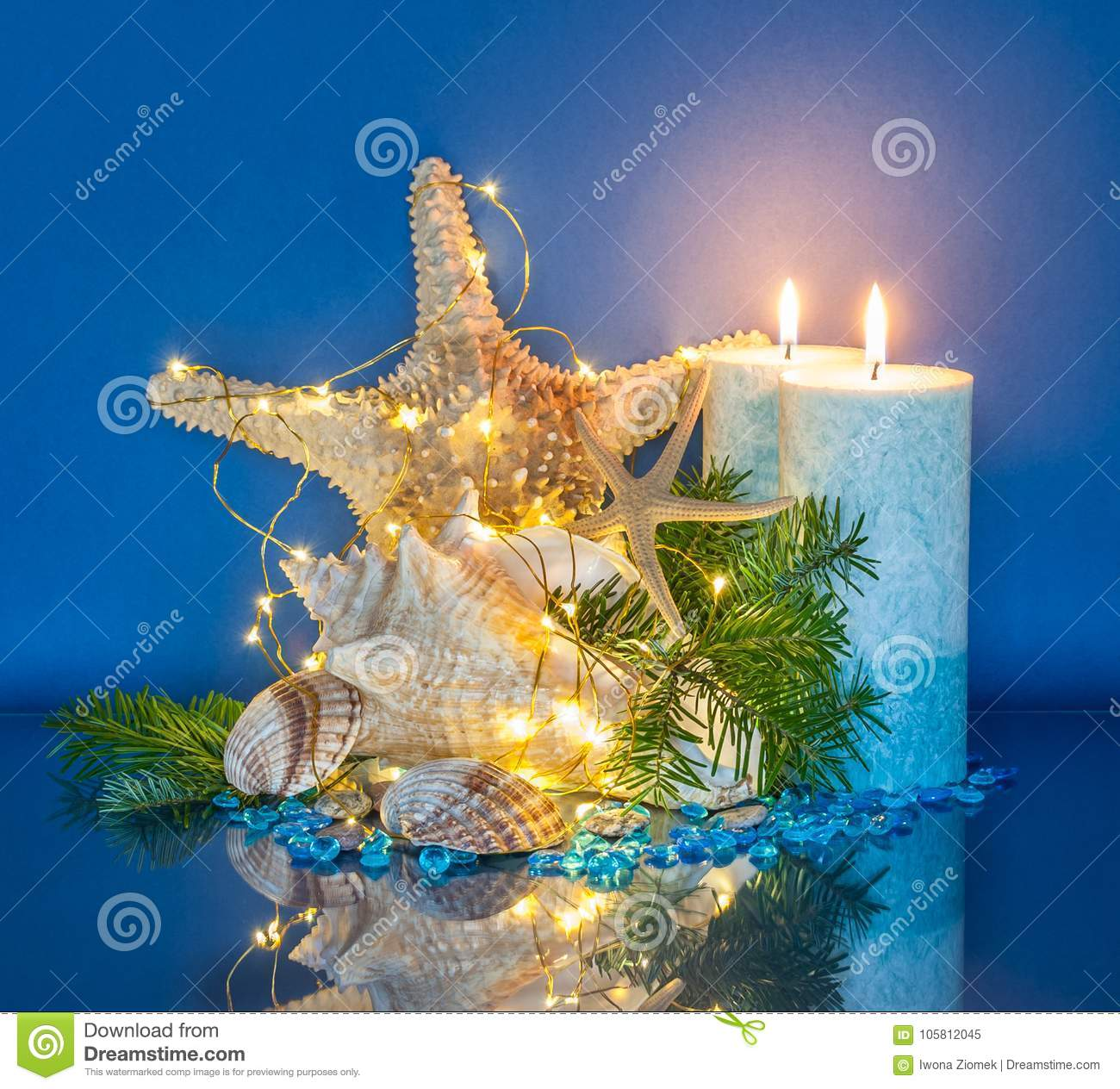 marine christmas decoration with fairy lights blue candles seashell and starfish