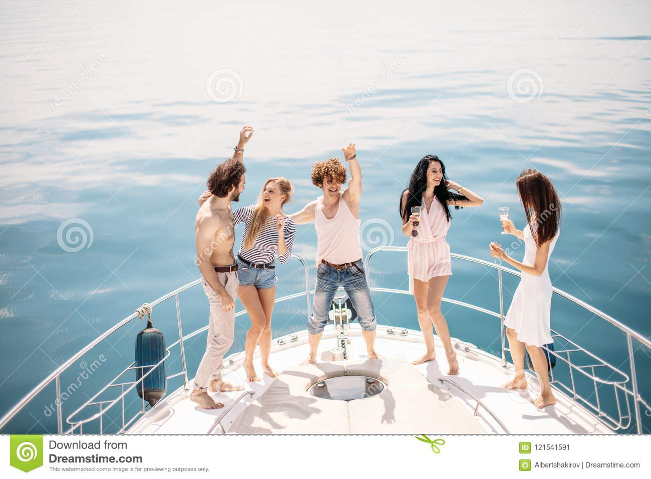Marine cruise and vacation - youngsters with champagne glasses on boat or yacht