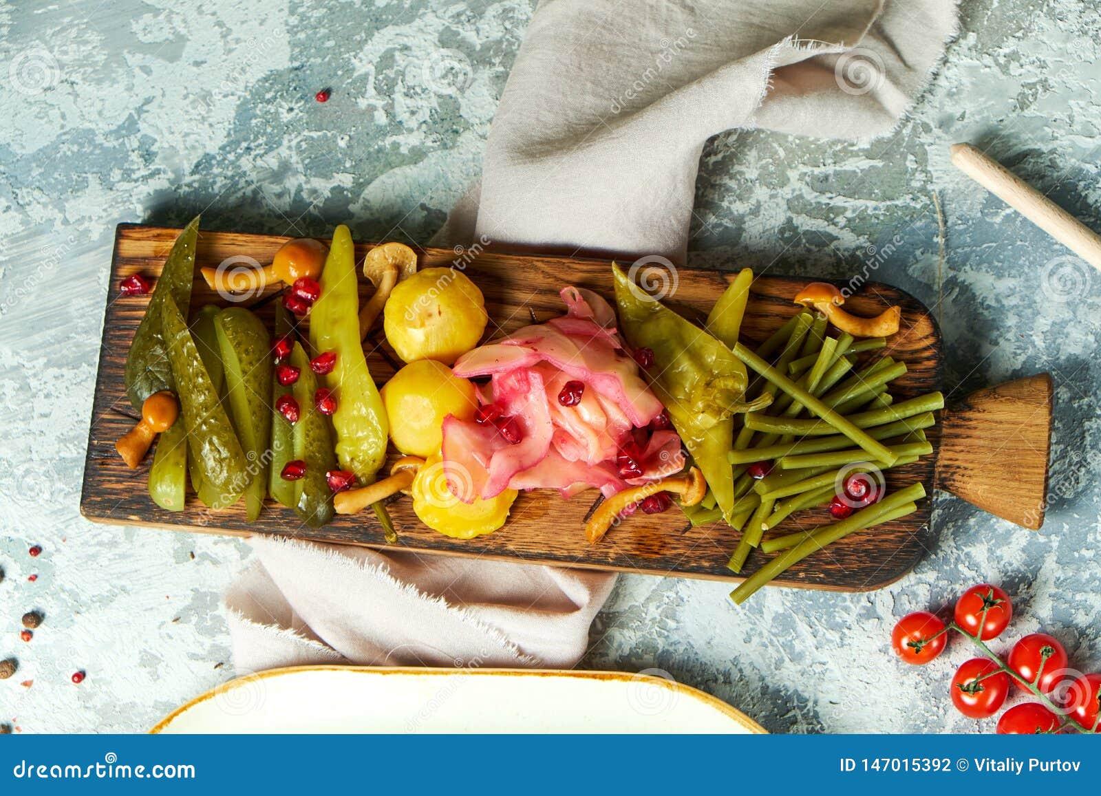 Mariniertes Gemüse auf einem hölzernen Brett Sch?ne Servierteller Hellgrauer Hintergrund Hochzeitsabendessen mit Rollenfleisch ra