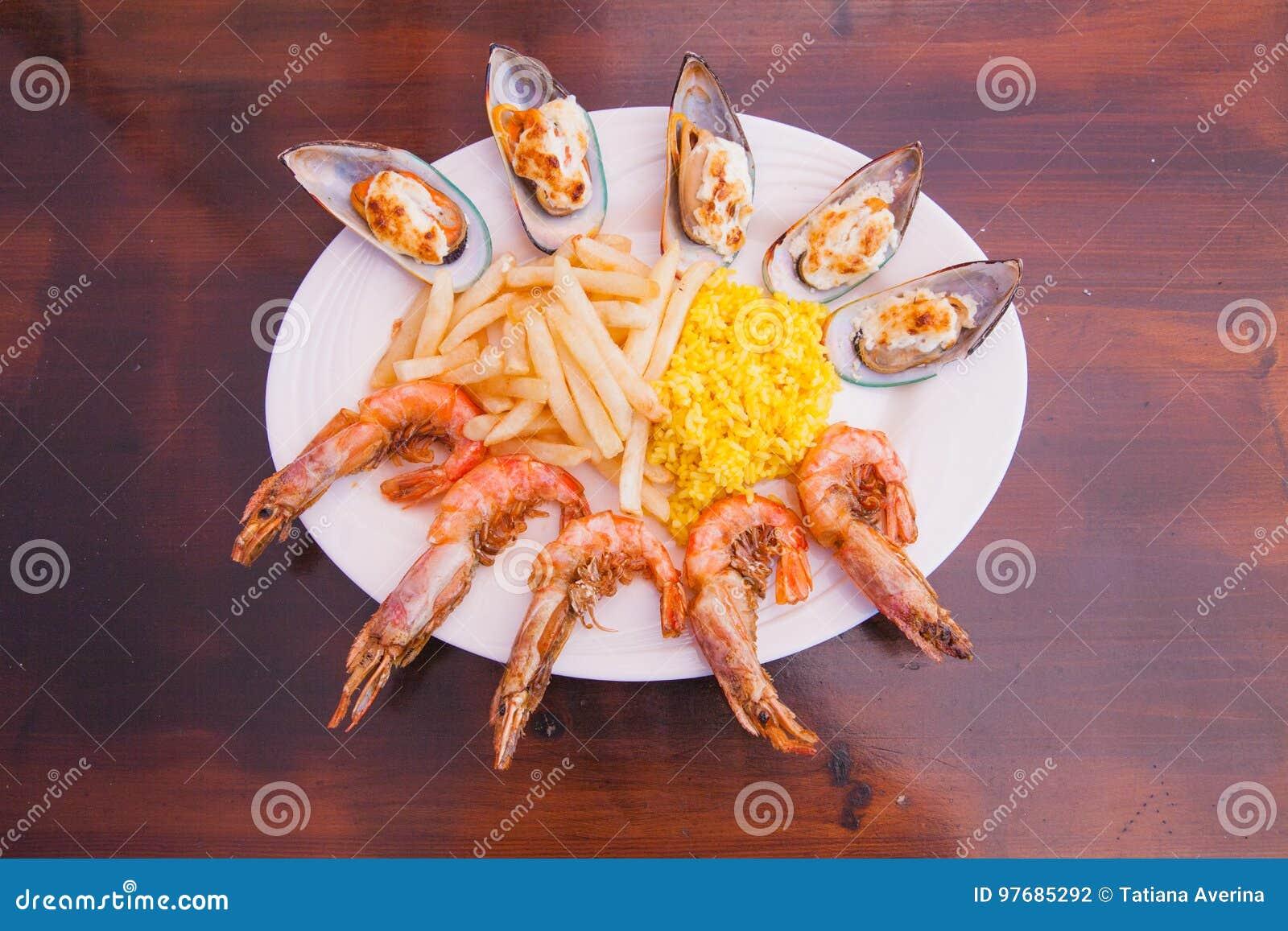 Mariscos con las patatas fritas y el arroz