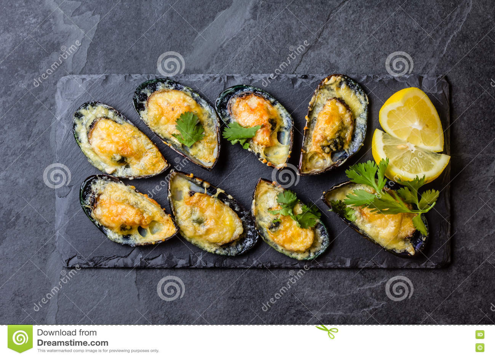 Mariscos Mejillones cocidos con queso y el limón en cáscaras