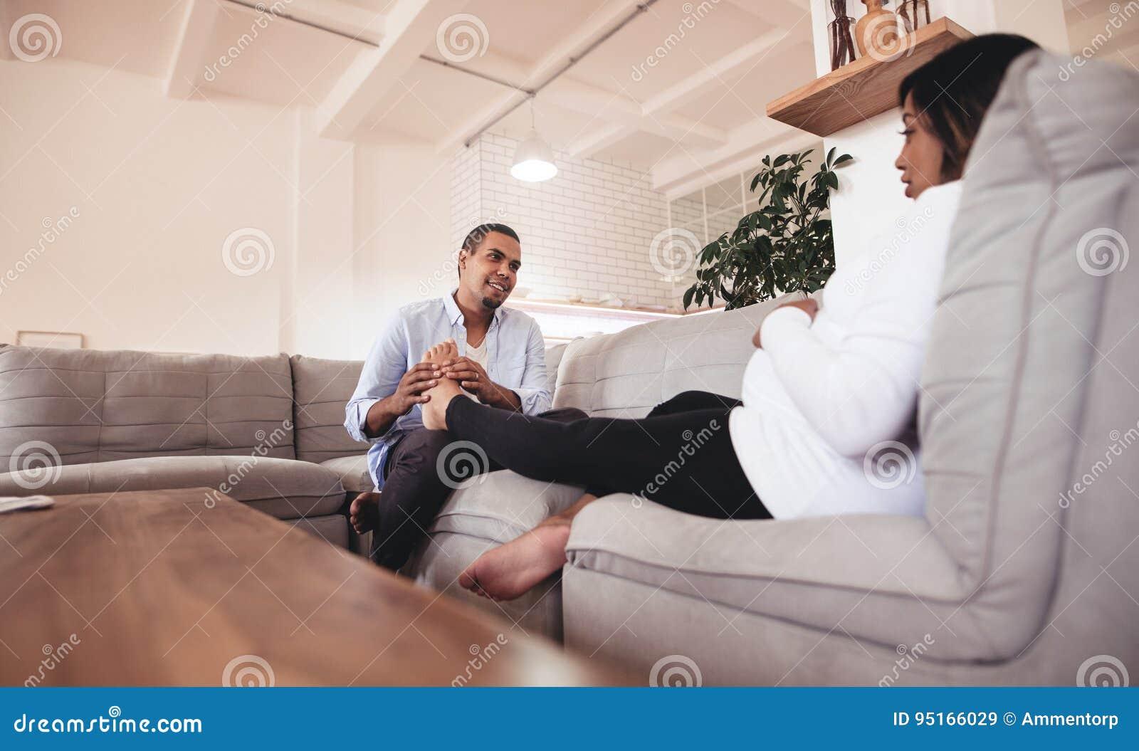 Marito che massaggia le sue gambe incinte della moglie