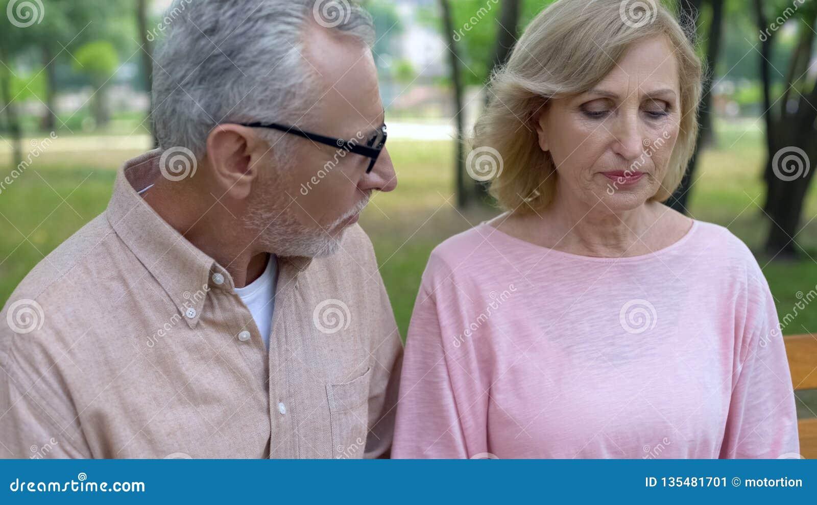 Marito invecchiato di amore che sostiene aria aperta triste della moglie, scuse maschii, crisi di relazione