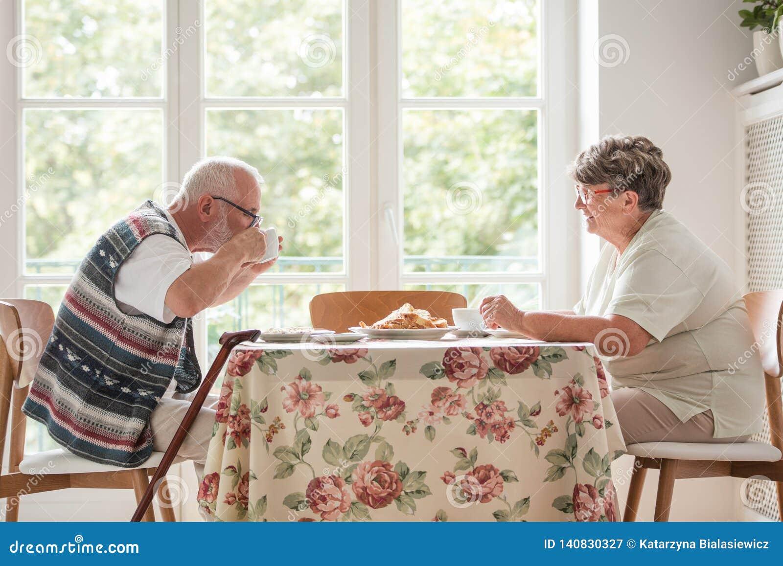 Marito più anziano e moglie che hanno un tè e un dolce insieme alla tavola