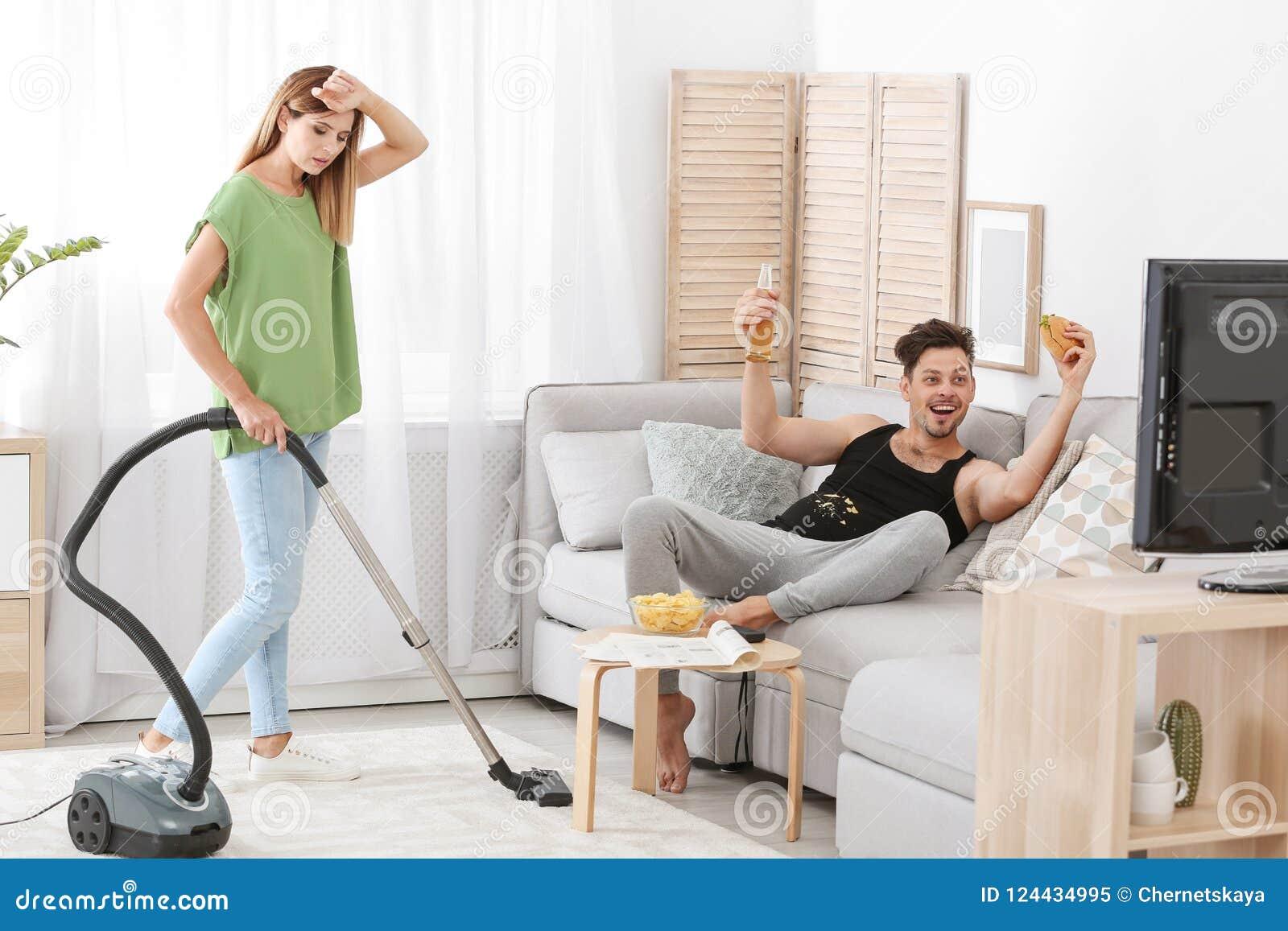 Marito pigro che guarda TV e la sua pulizia della moglie