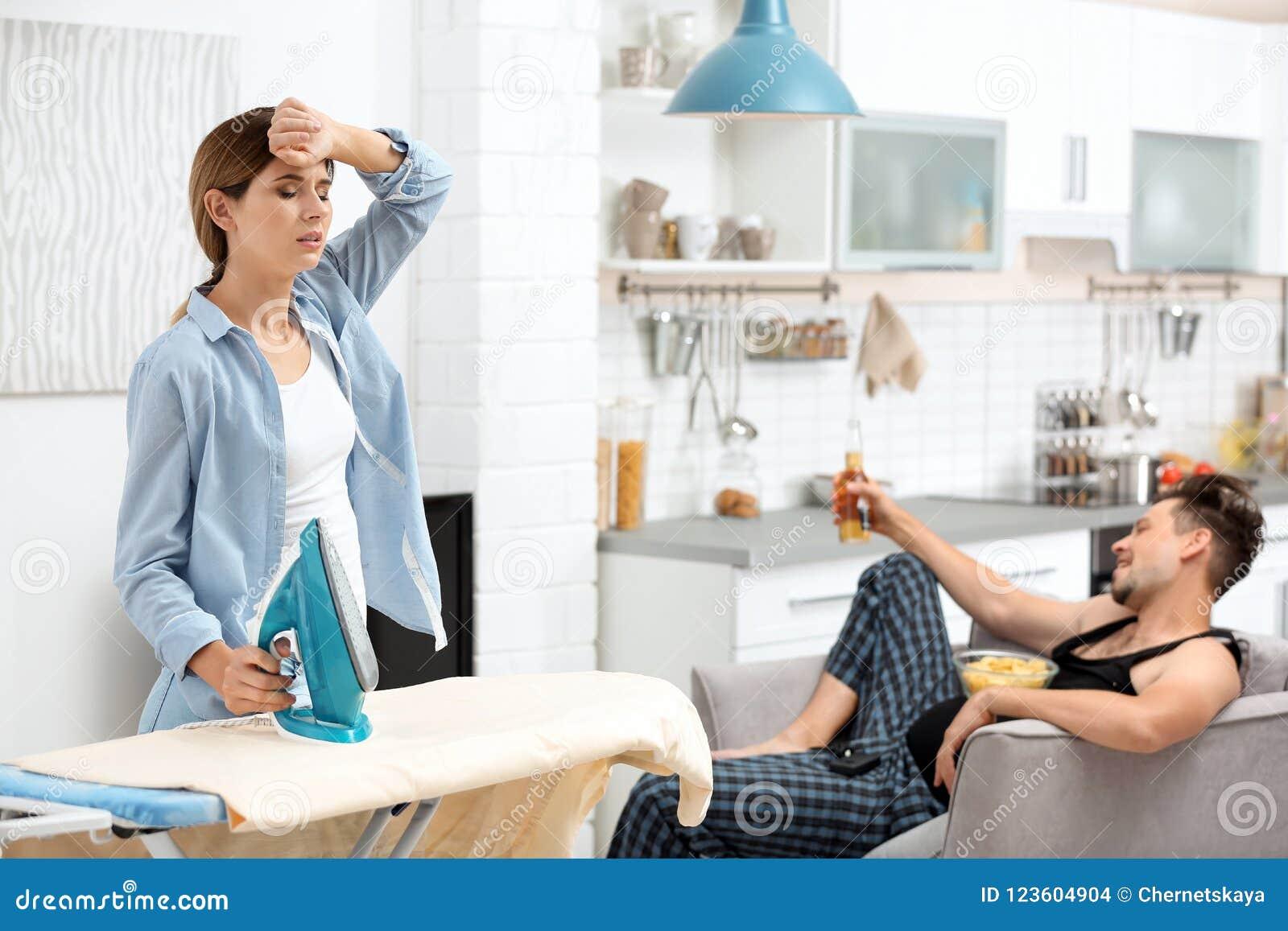 Marito pigro che guarda TV e suo rivestire di ferro della moglie