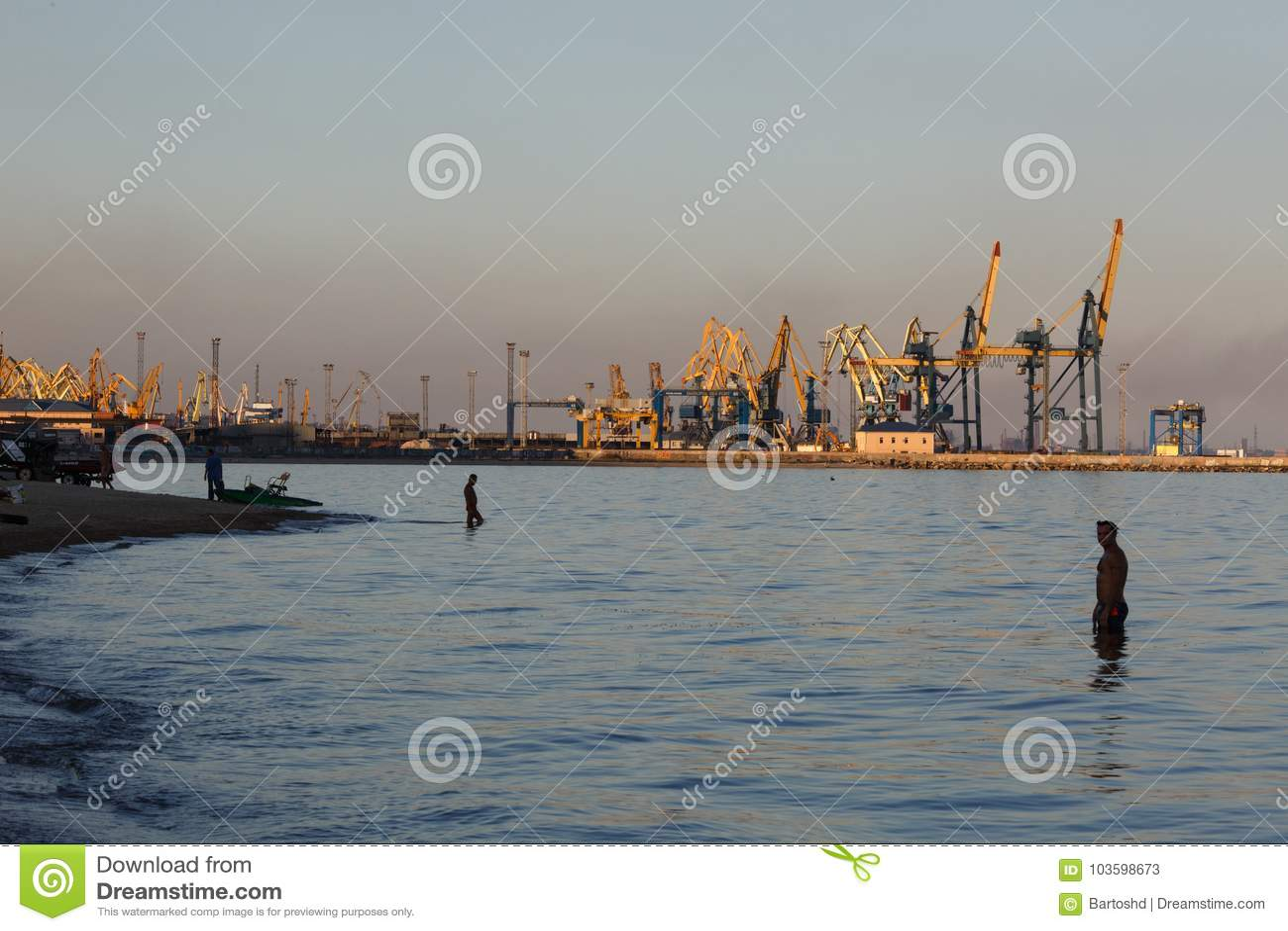 MARIUPOL, DE OEKRAÏNE - SEPTEMBER 5, 2016: Vele groot kranensilhouet in de haven bij gouden licht van zonsondergang
