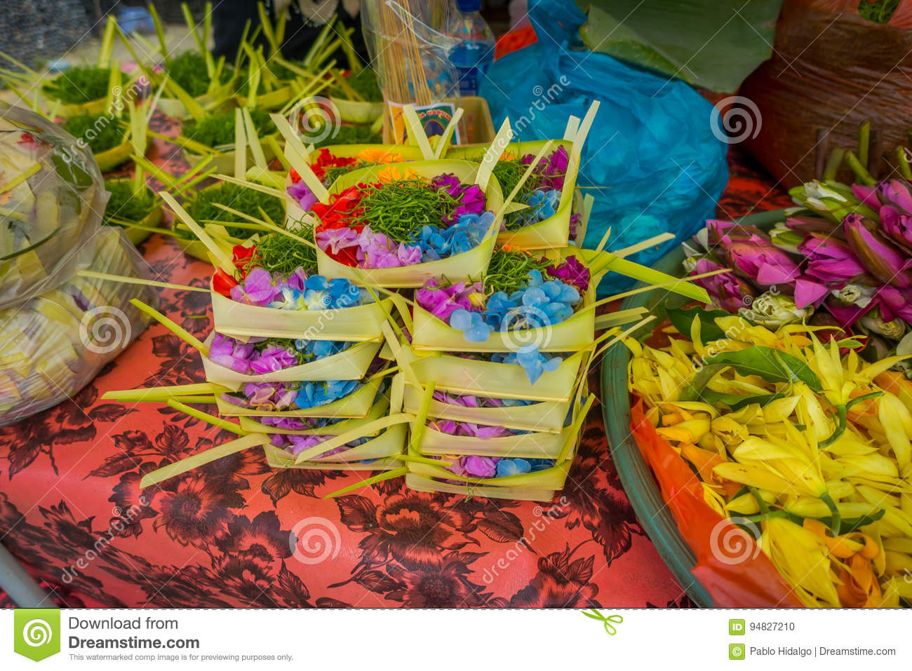 A market with a box made of leafs, inside an arrangement of flowers on a table, in the city of Denpasar in Indonesia