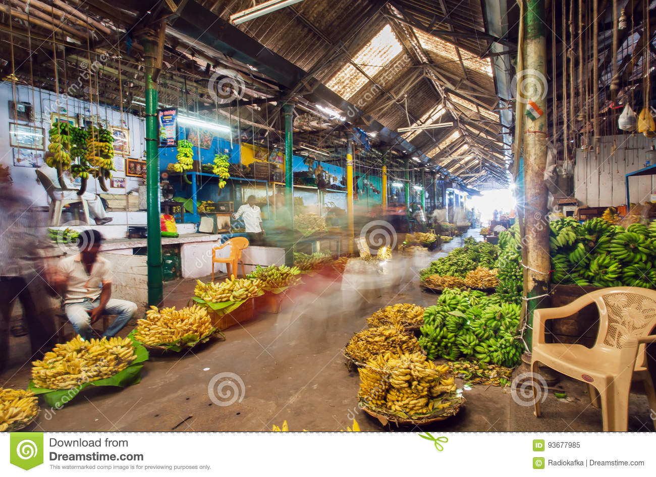 Market traders and buyers walk in motion blur in a storehouse with bananas and fruits